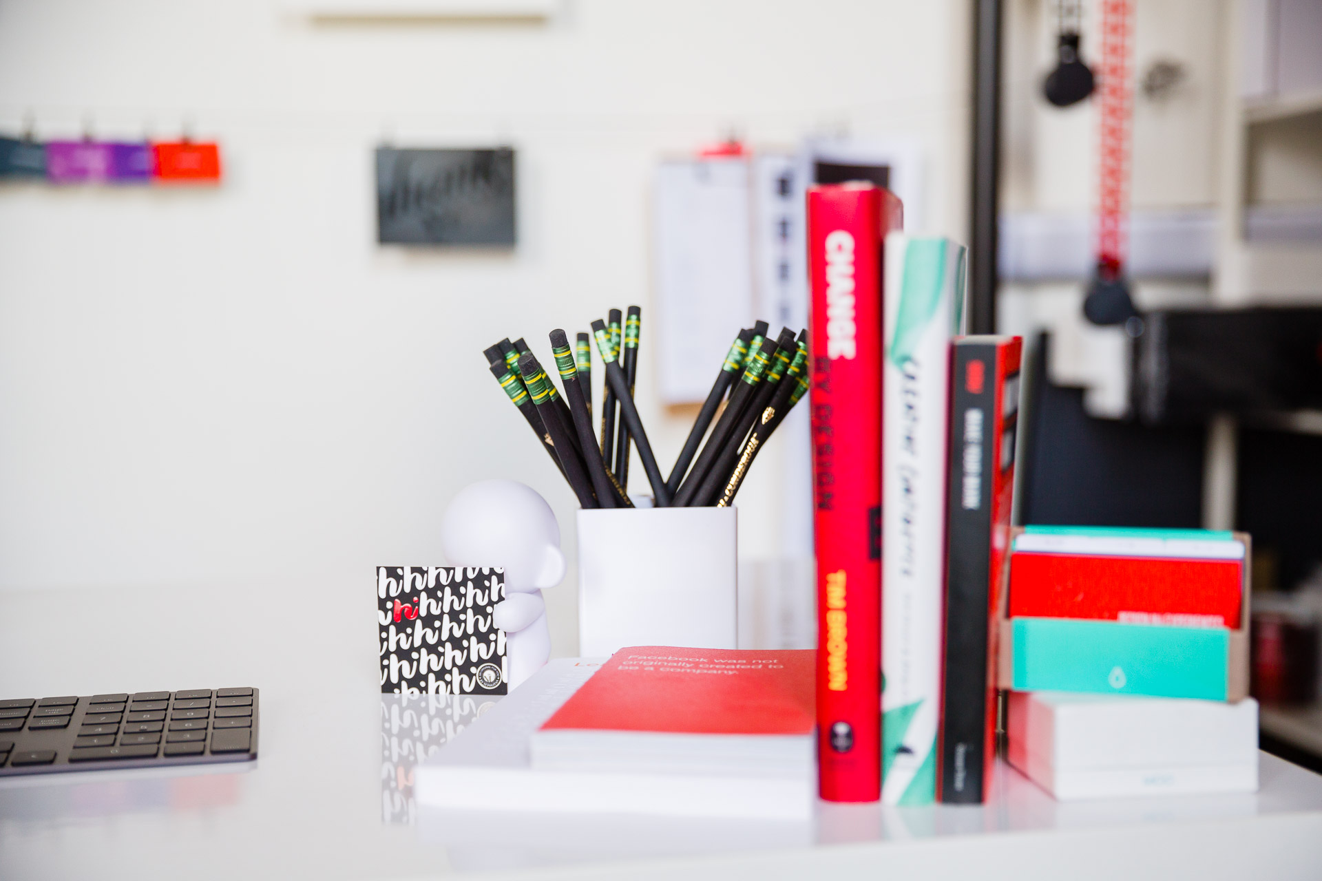 Design books, a cup of pencils, business cards, and a white munny figurine holding a hi card sitting on a desk