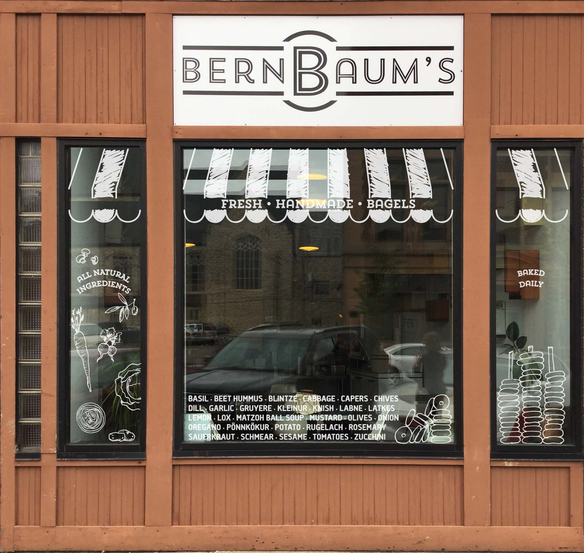 Concept for windows with hand-drawn white awning, listing of ingredients, and illustrations of ingredients and bagels
