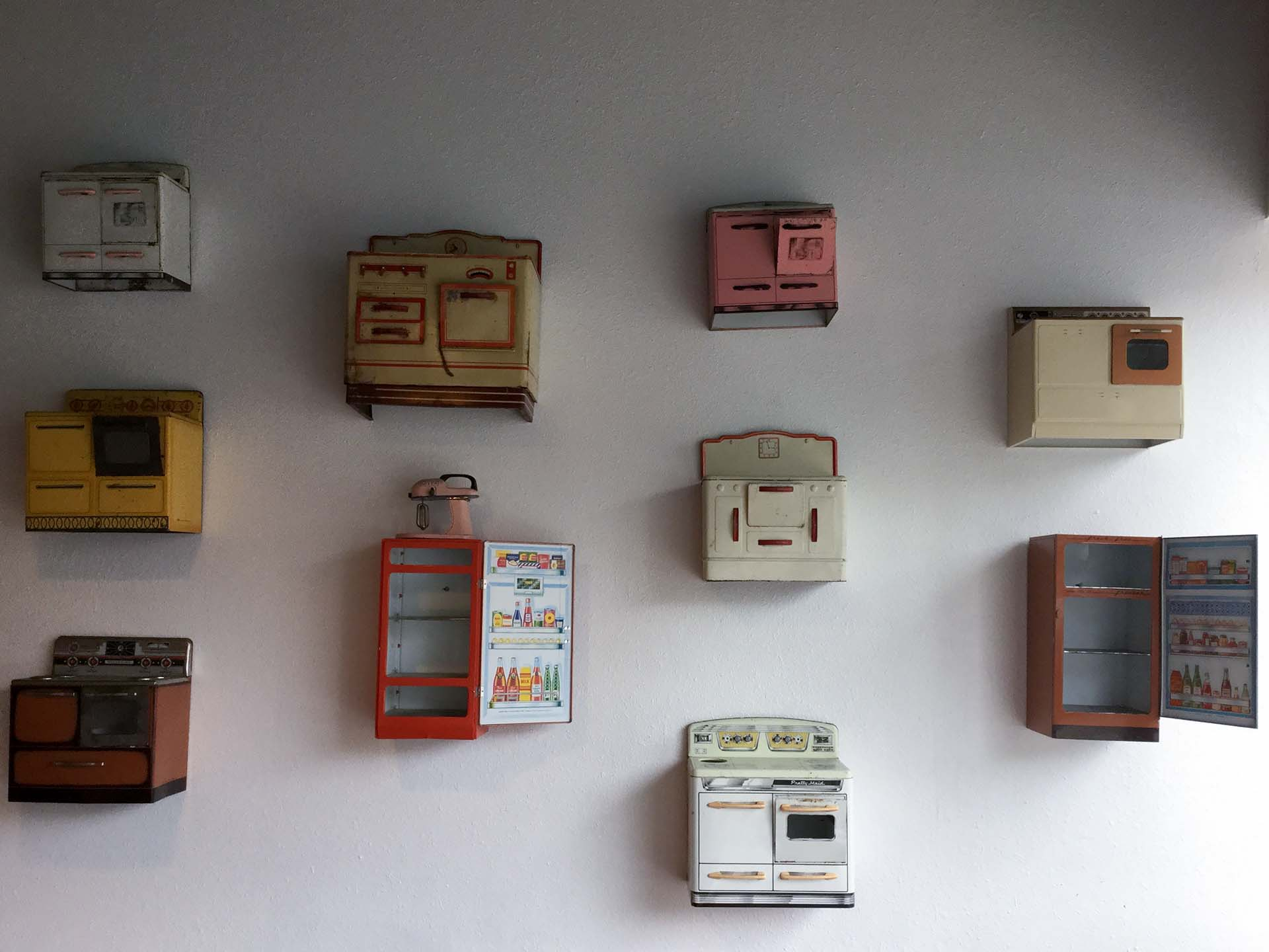 Metal toy appliances mounted on a white wall