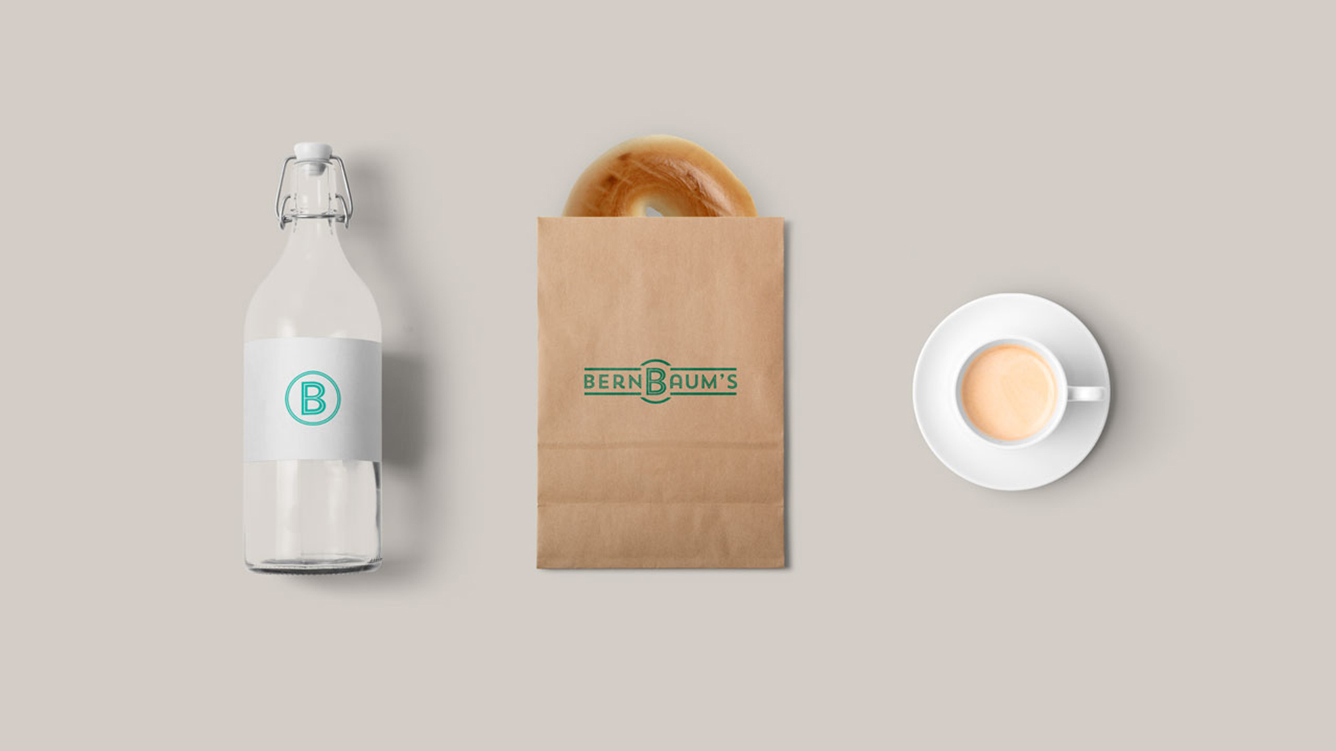BernBaum's icon printed on water bottle label, logo printed in green on kraft bag with bagel poking out, and cup of coffee