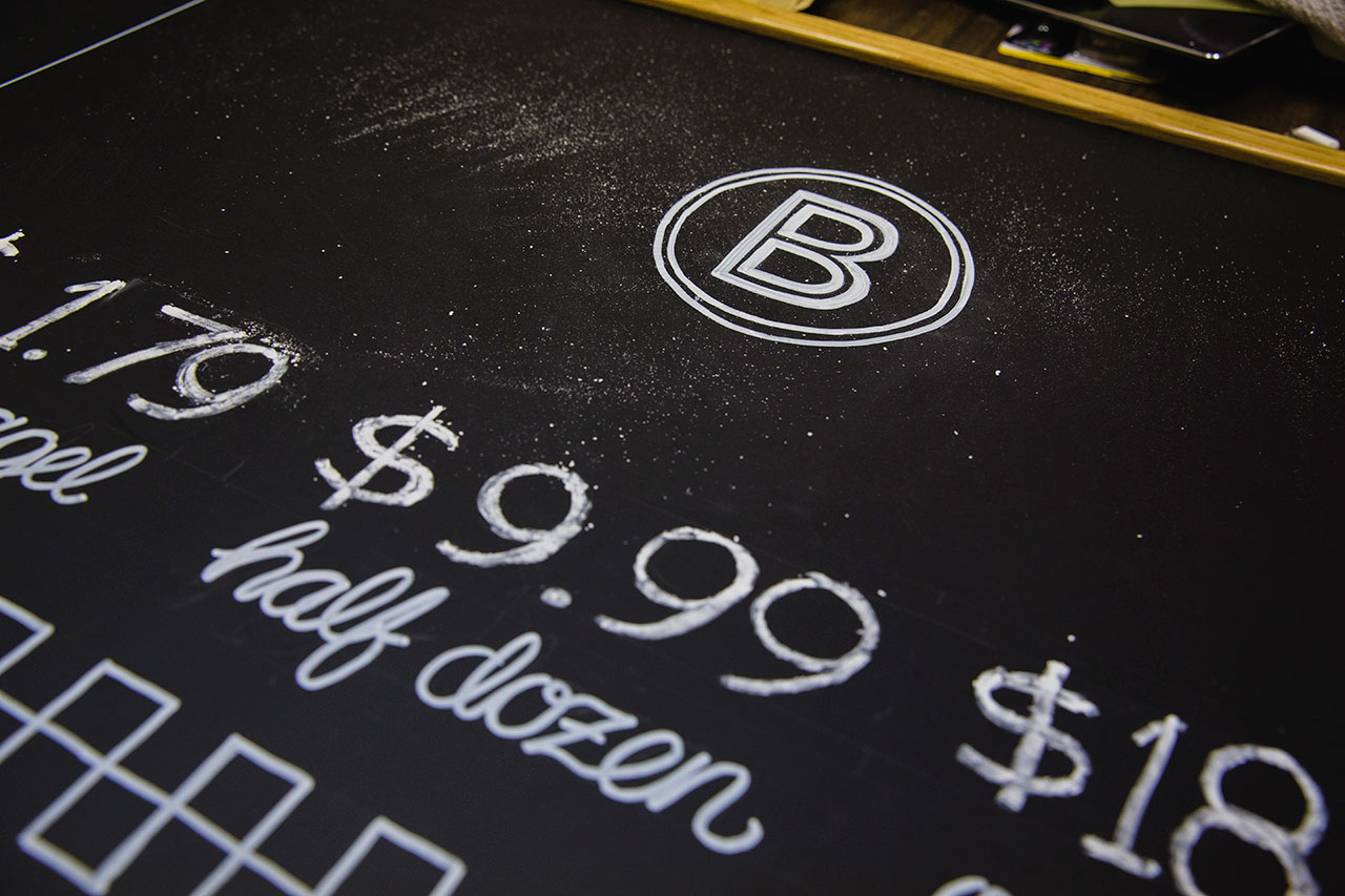 Close-up of chalkboard displaying BernBaum's B icon and pricing for bagels