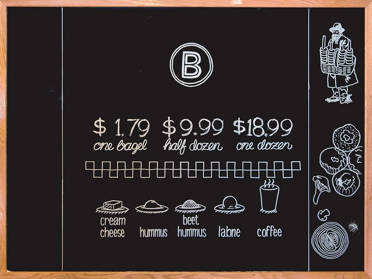 Black chalkboard with white chalked BernBaum's B logo, pricing for bagels, and illustrations of spread options