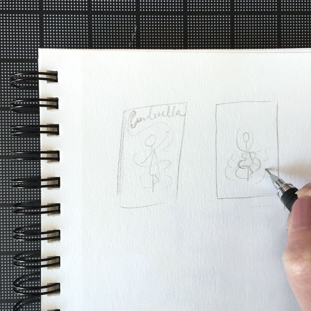 A hand sketching layouts for Cinderella poster in a sketchbook