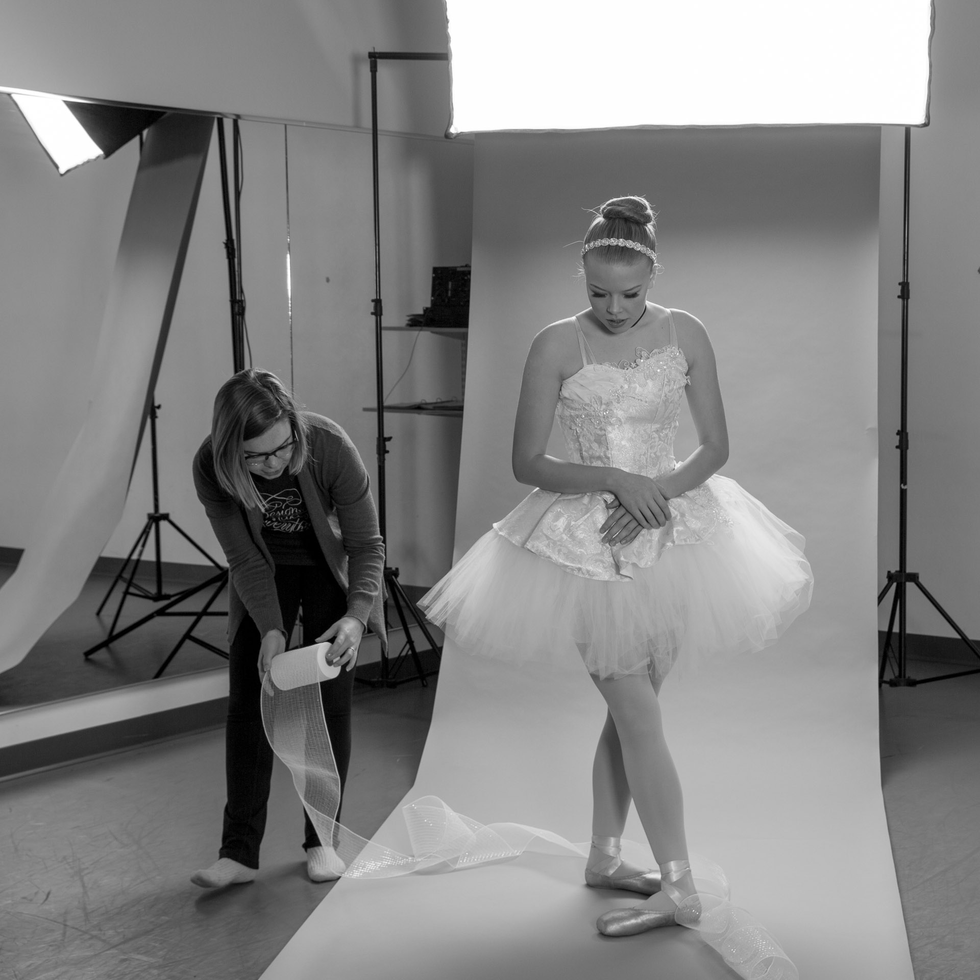 Woman draping tulle around the feet of ballerina dressed in Cinderella tutu in front of photo backdrop