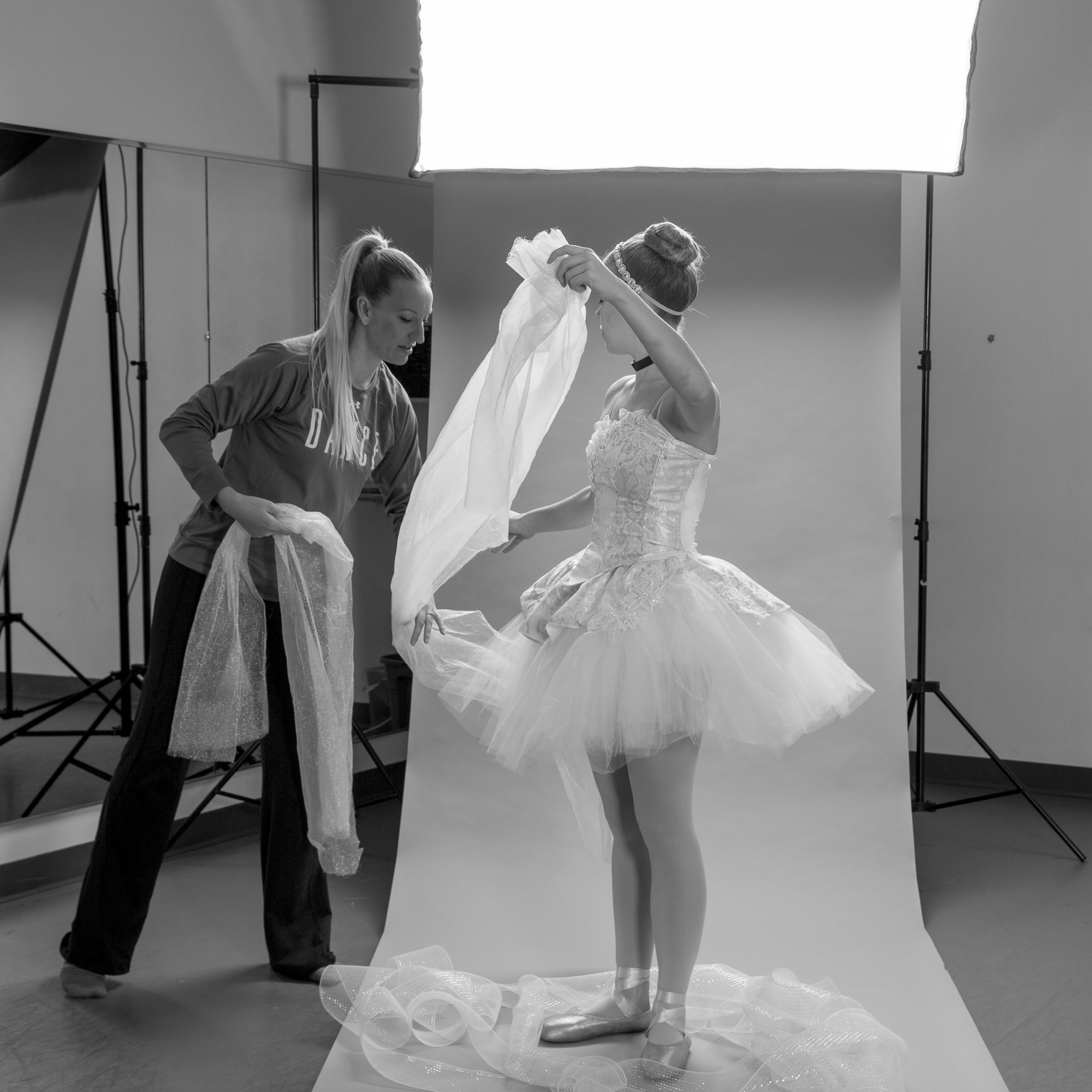 Woman draping tulle and ballerina dressed in Cinderella tutu assisting in front of photo backdrop