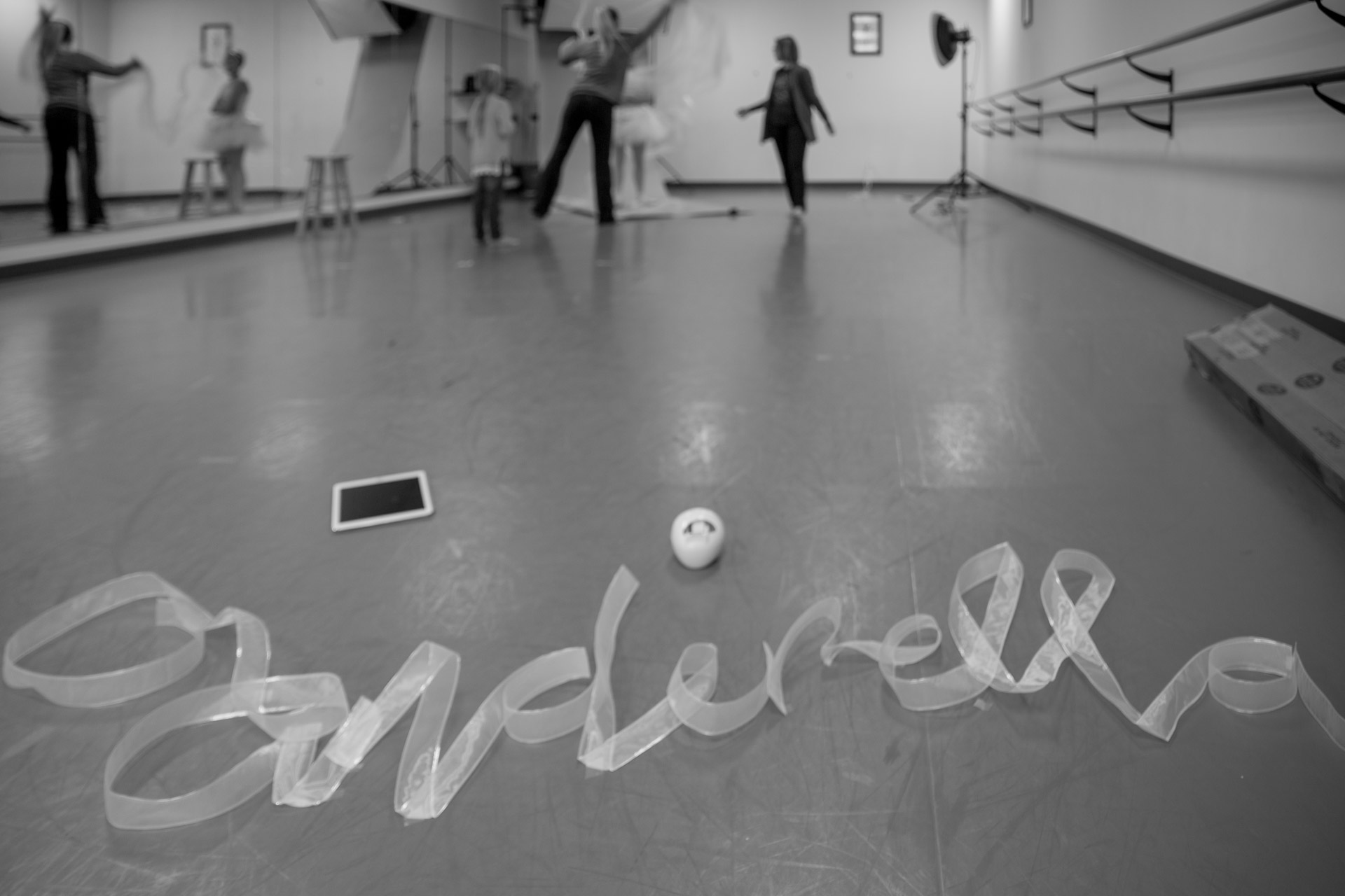 The word Cinderella made from ribbon on floor of dance studio with women in background preparing set