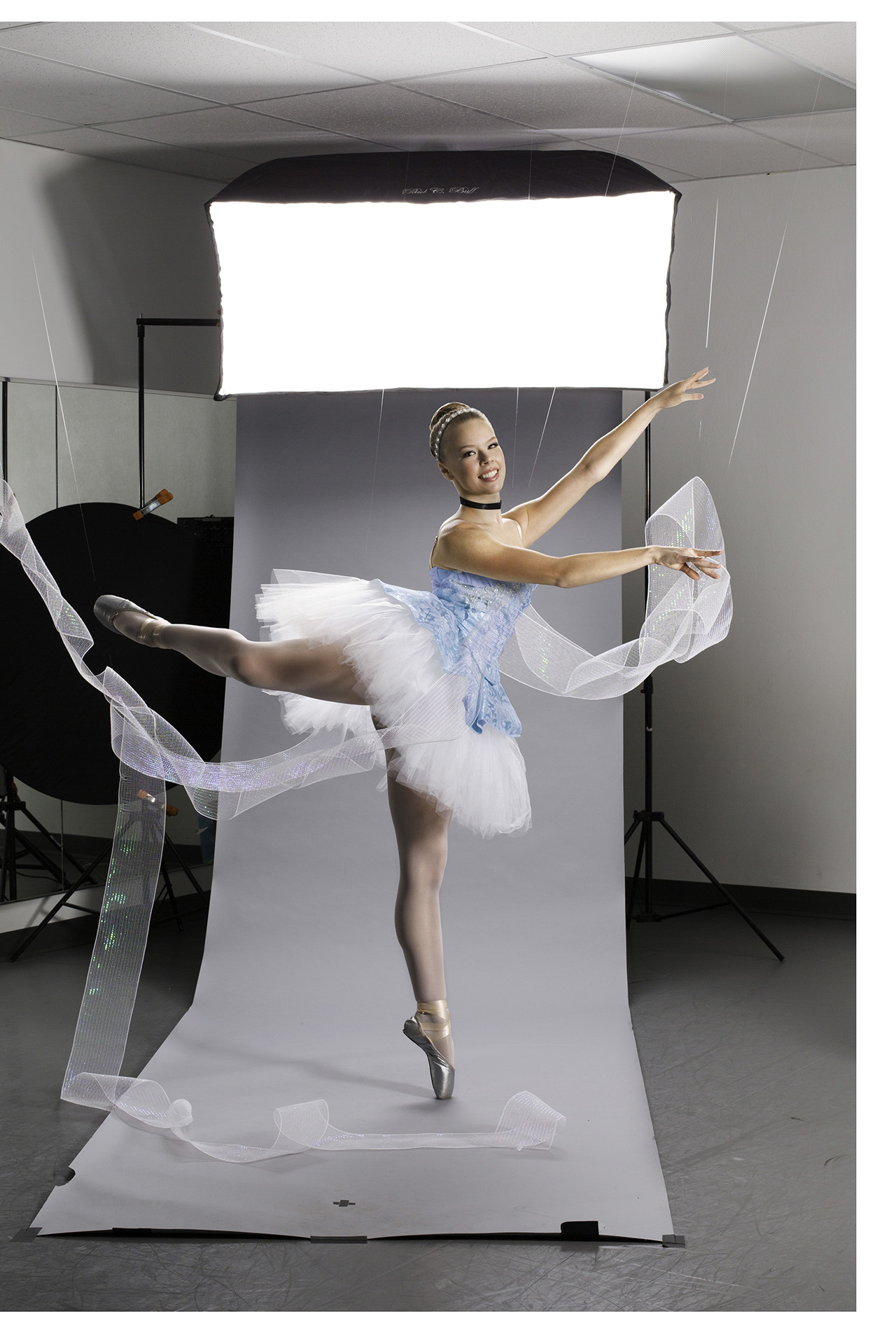 Ballerina dressed in Cinderella tutu poses in front of photo backdrop with tulle draped around her