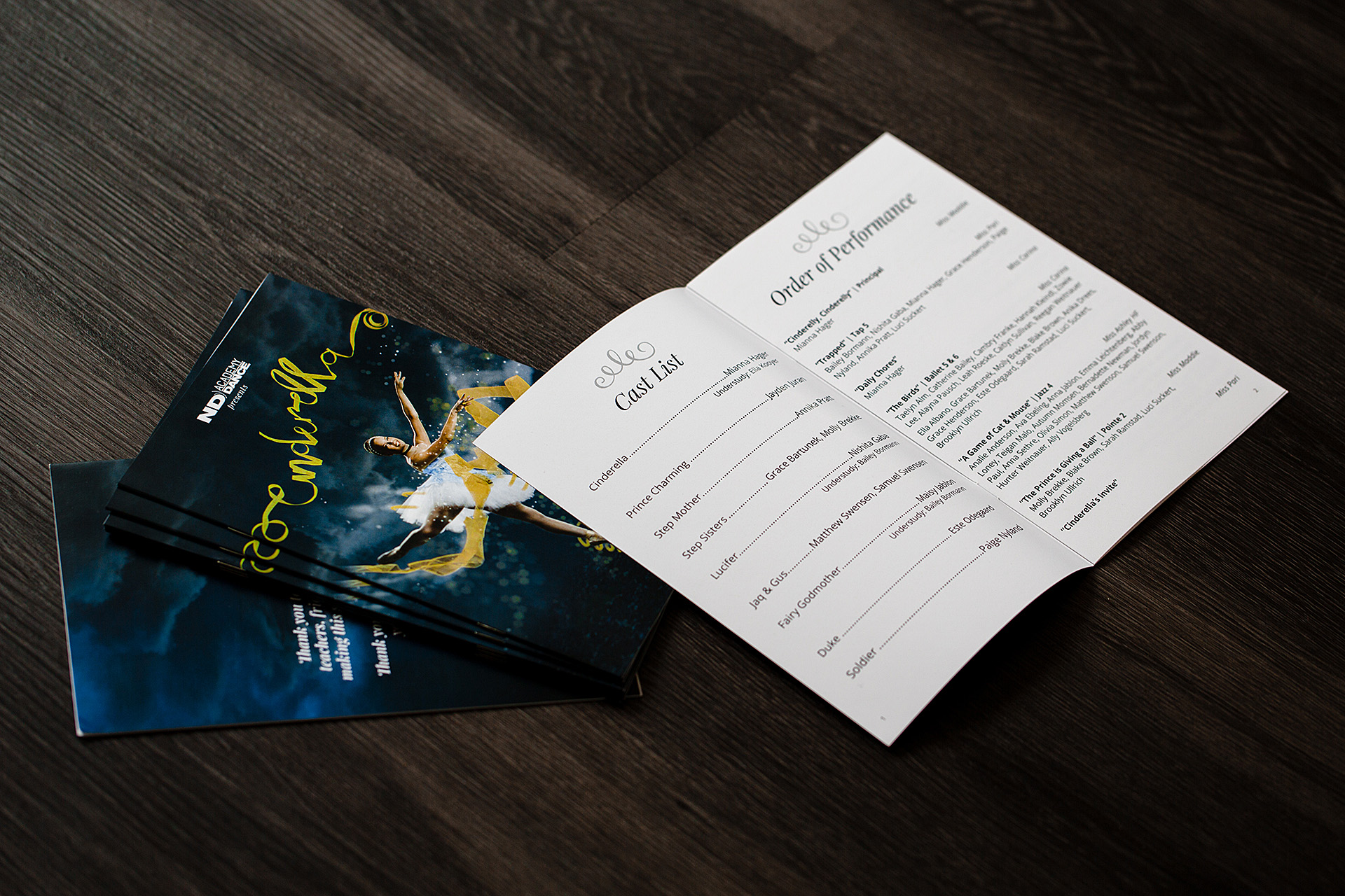 A stack of Cinderella recital programs with an open program displaying order of performance laying on a wood floor