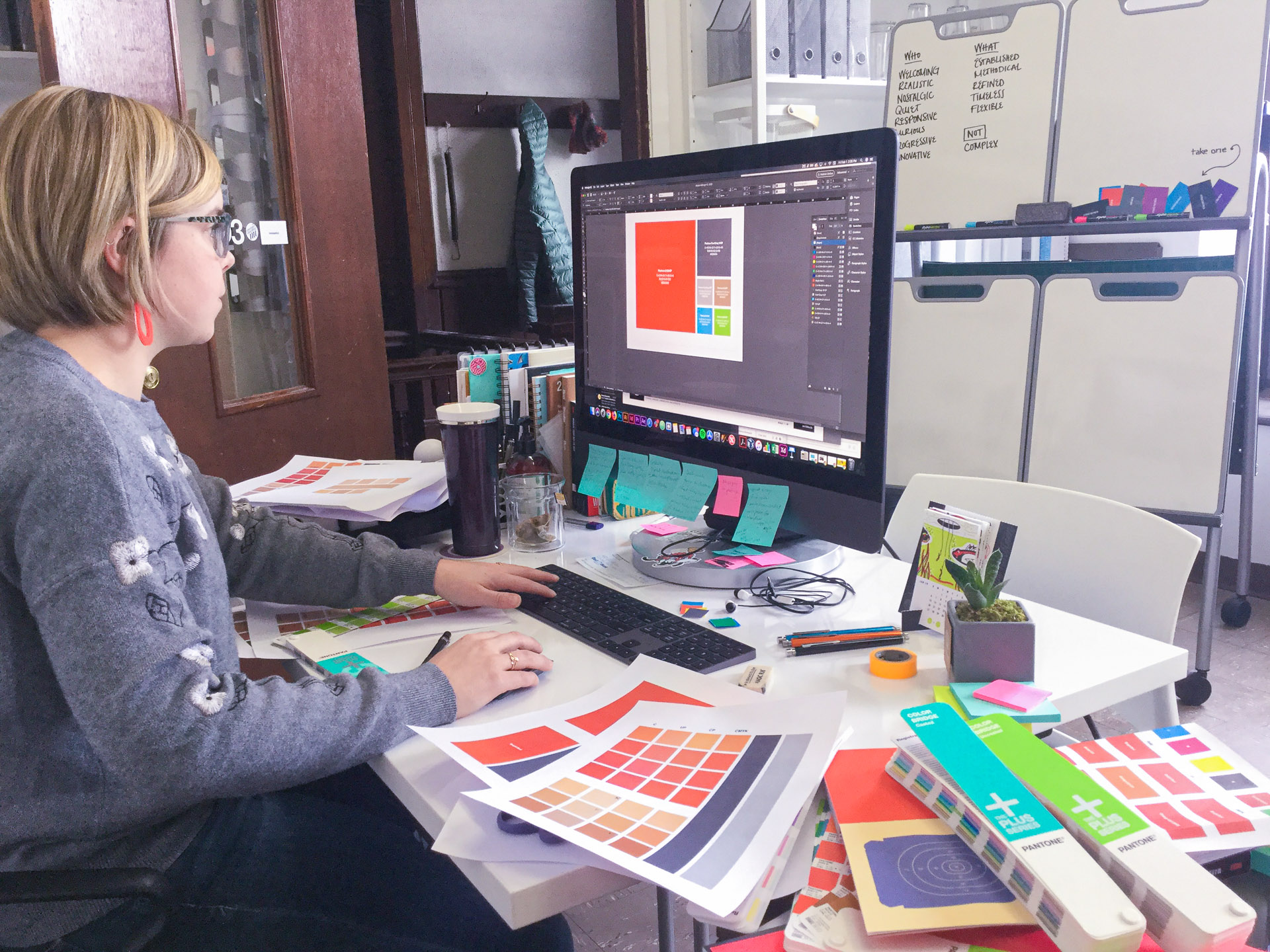 Woman working on the computer looking at the CLLA color scheme on the screen with Pantone color swatch books on her desk