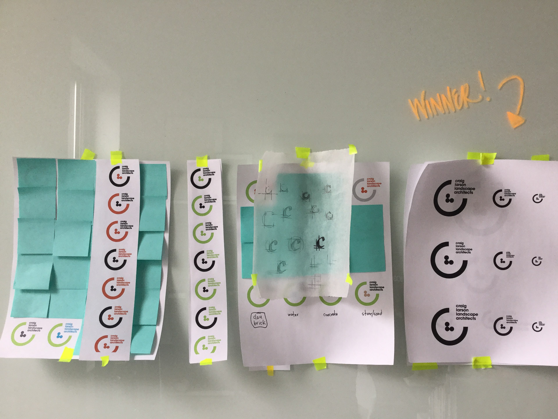 Logo concepts printed on letter paper and taped to a white board with blue post-its stuck on the papers