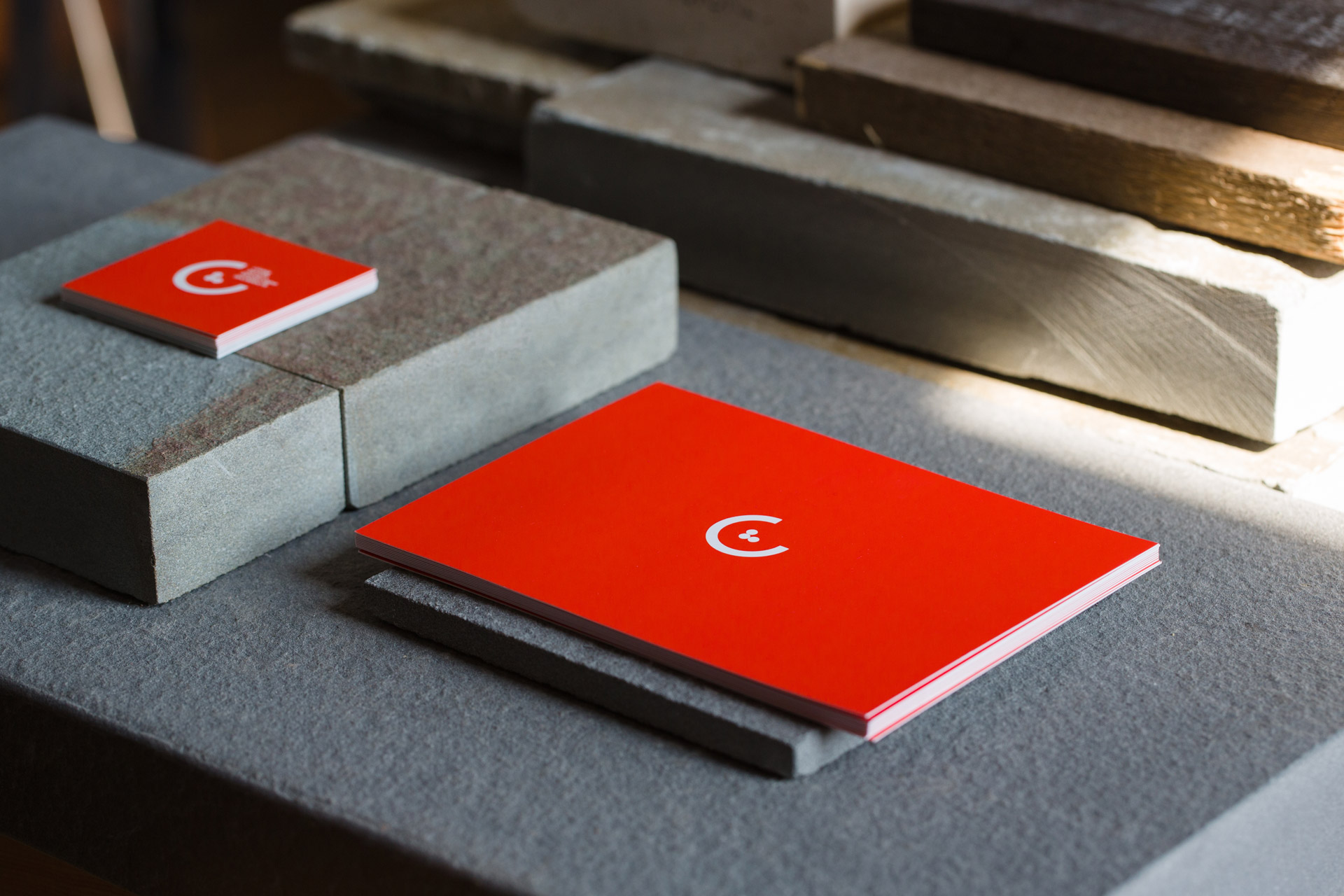 Stacks of red postcard and square business card displaying CLLA logomark sitting on blocks of stone