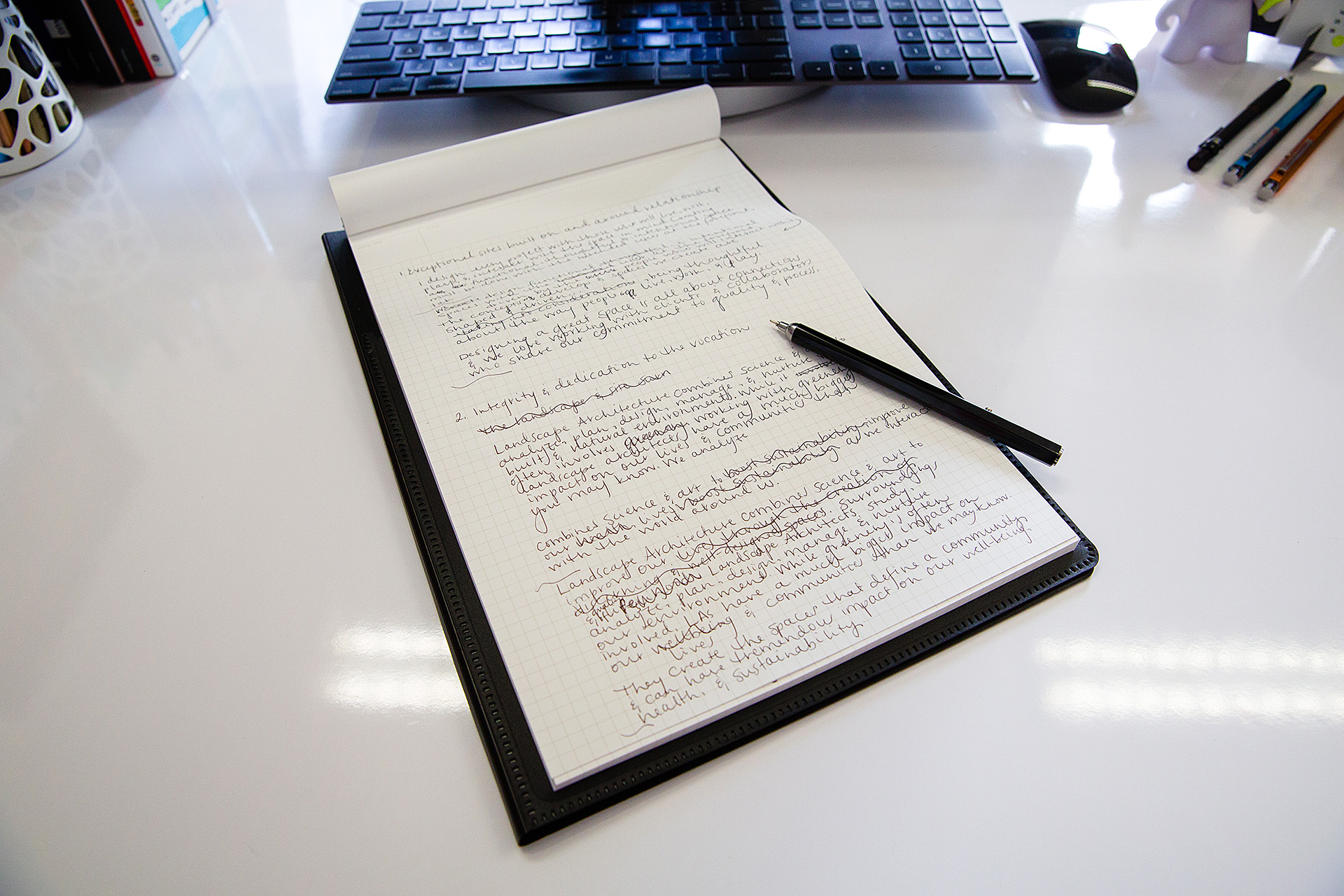 Pen and notepad displaying written content for website copy on white desk
