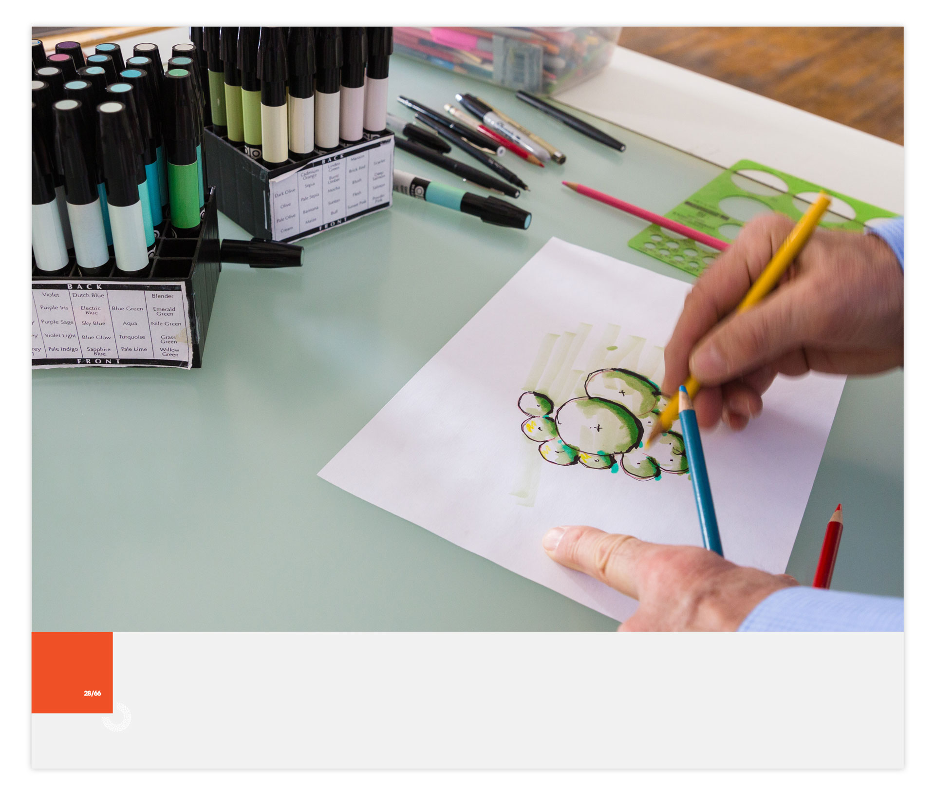 Man's hands drawing shrubs in architectural style and two boxes of markers on the table