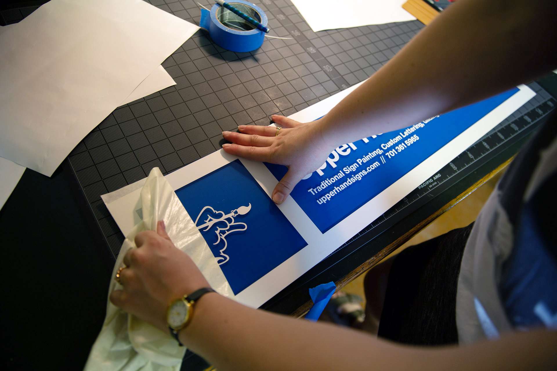 White vinyl for Upper Hand Signs being applied to acrylic with blue backing