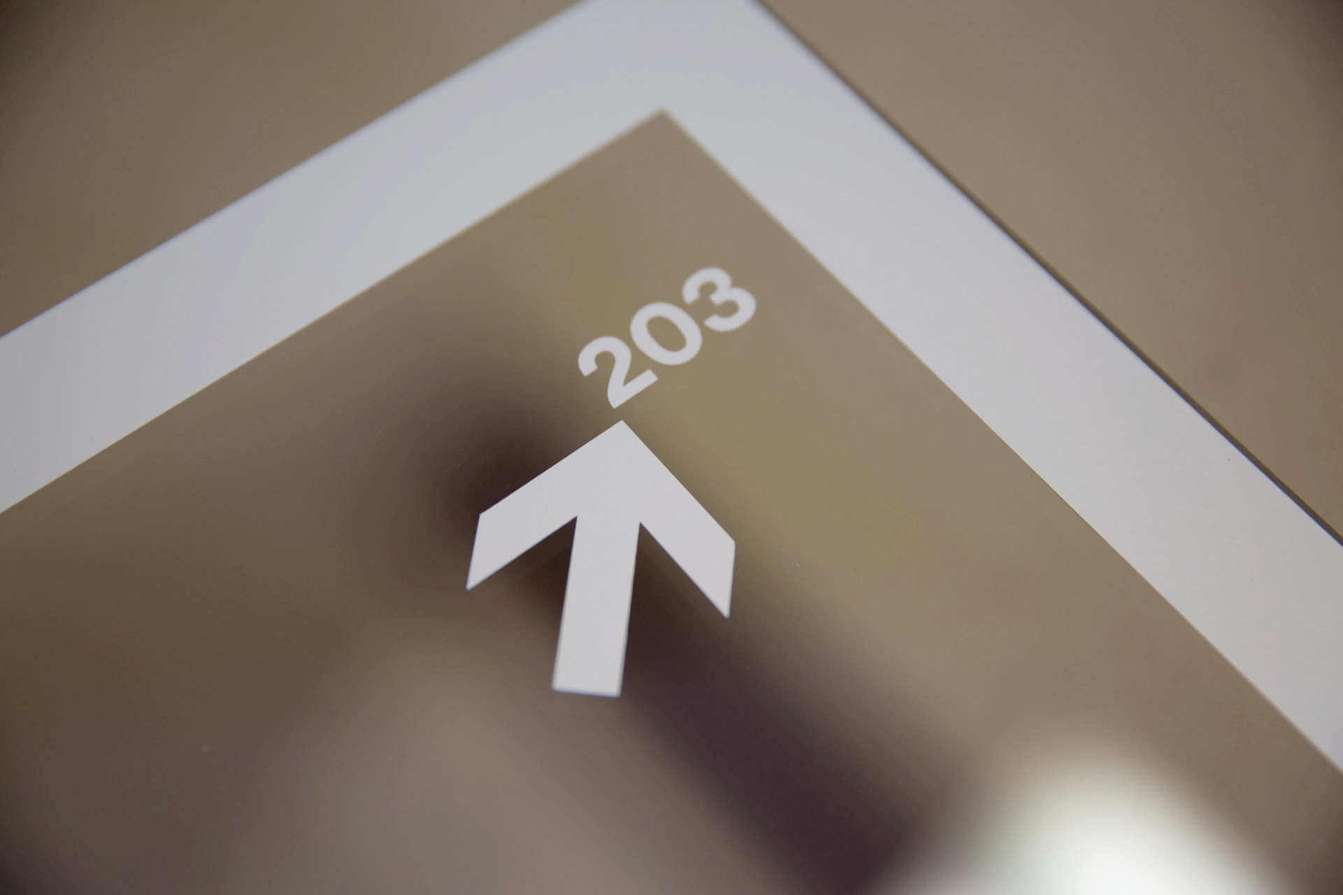 Close-up of white vinyl arrow, room number 203, and border on clear acrylic