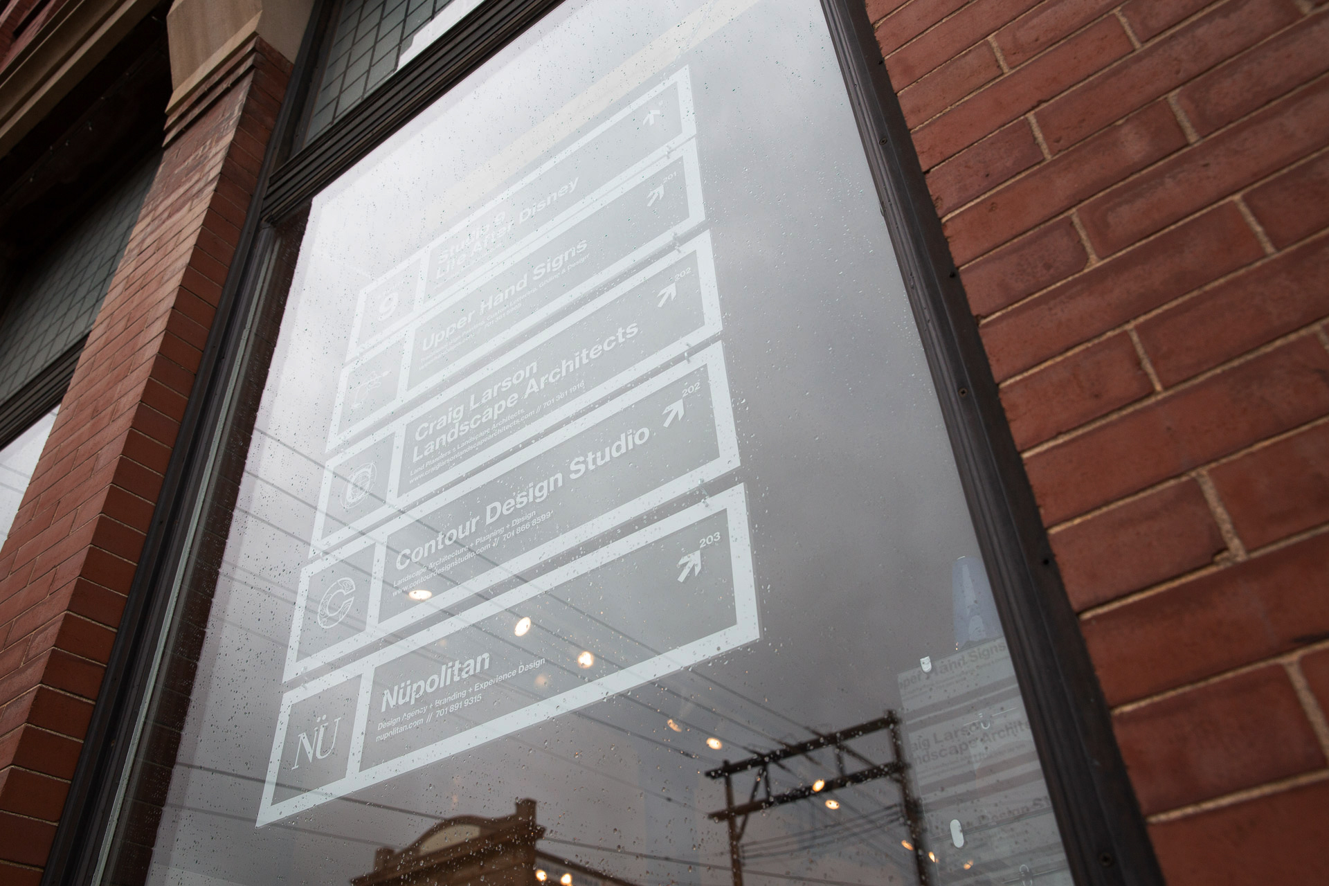 Five clear acrylic panels with white vinyl lettering hanging in the window of a brick building