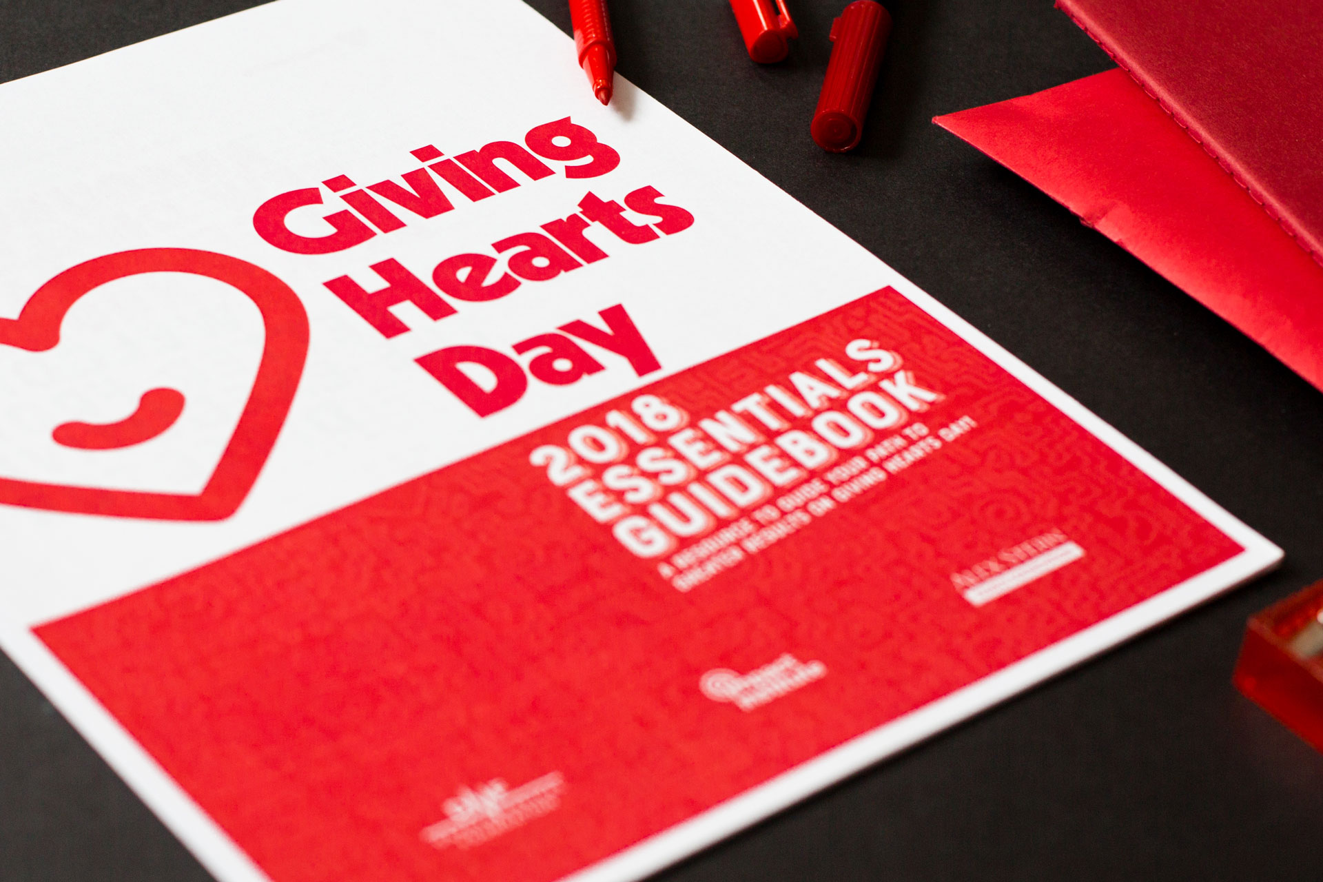 Close-up of Giving Hearts Day 2018 Essentials Guidebook printed laying on a dark background next to red journals and markers