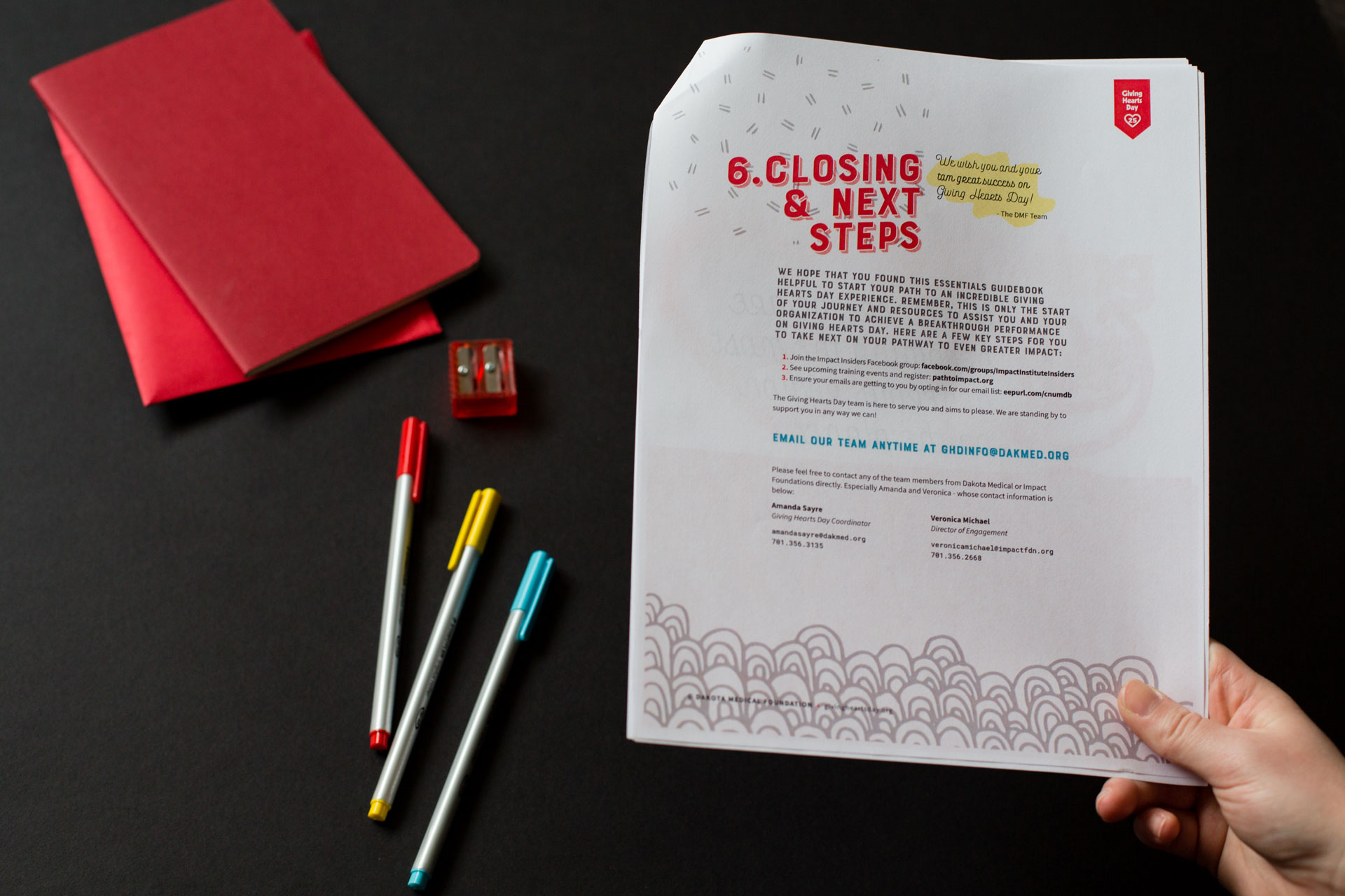 A hand holding the printed guidebook opened to interior page over a dark background next to red journals and markers