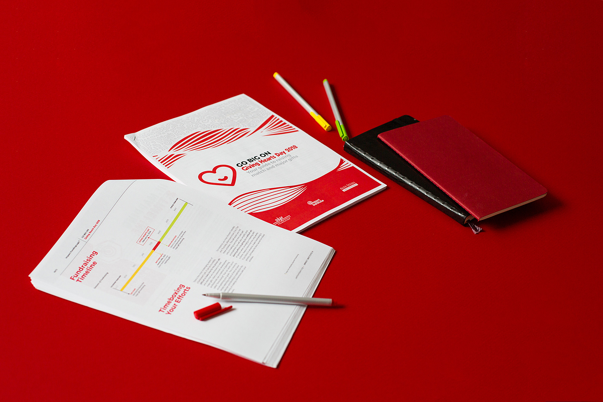 Two printed booklets laying on red background next to a black journal, red journal, and colored pens