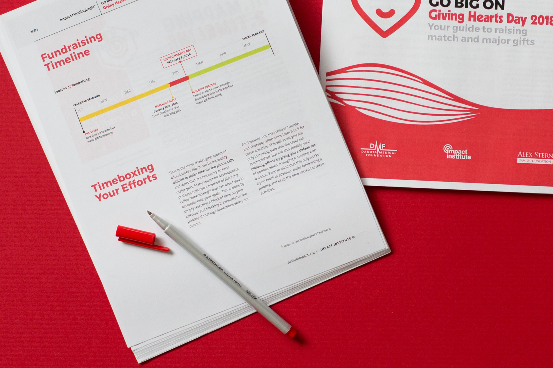 Close-up of two printed booklets and a red pen