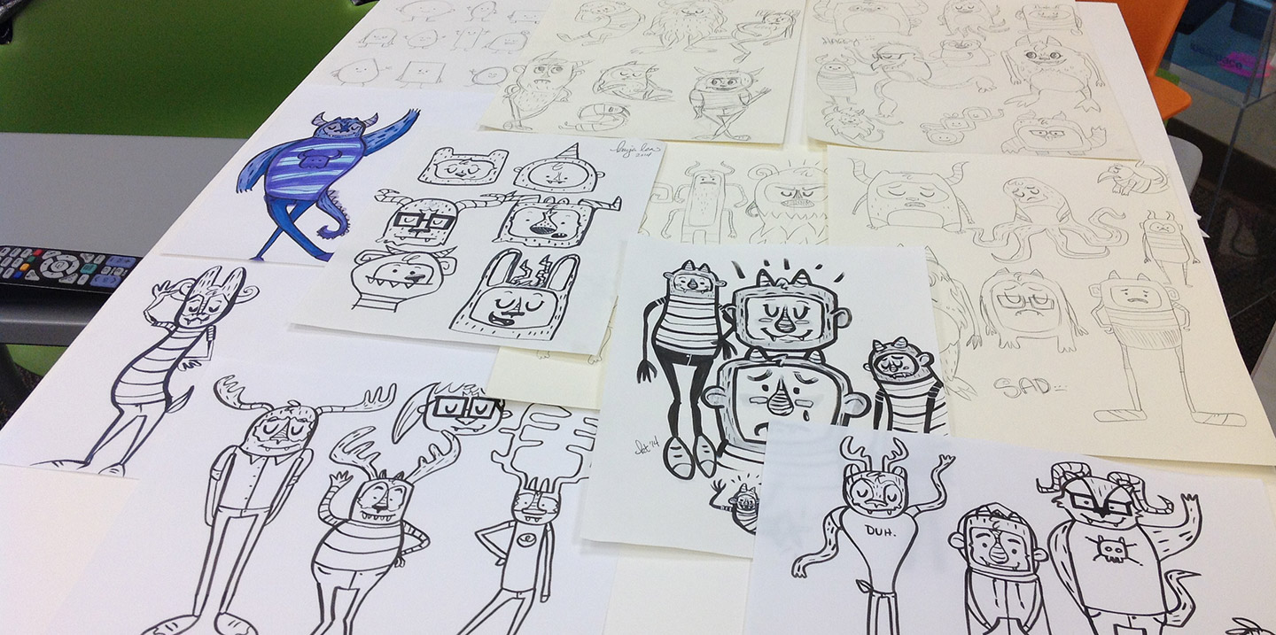 A table covered with sketches of cute monsters