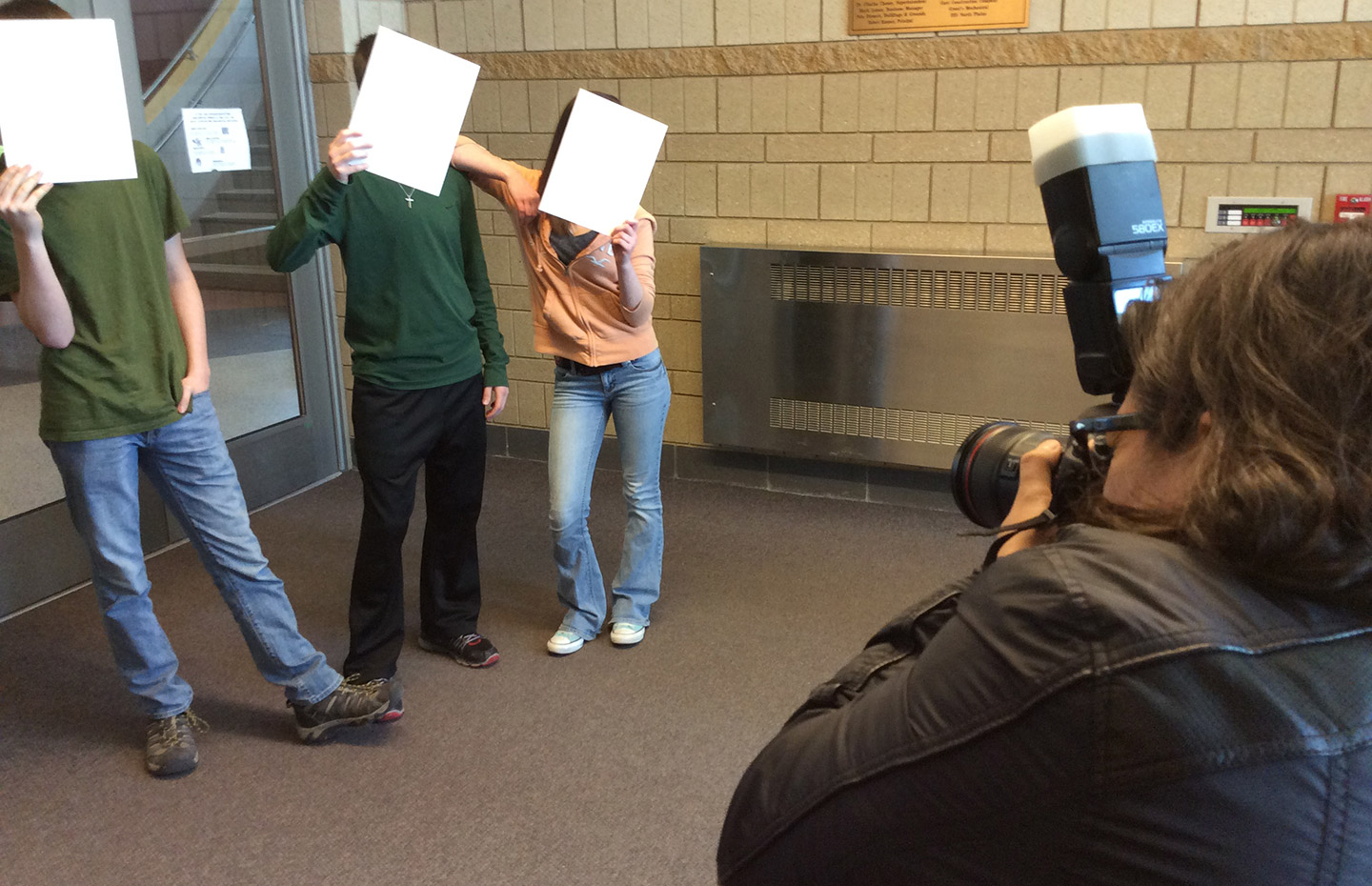 Man taking photo of three kids holding paper over their faces