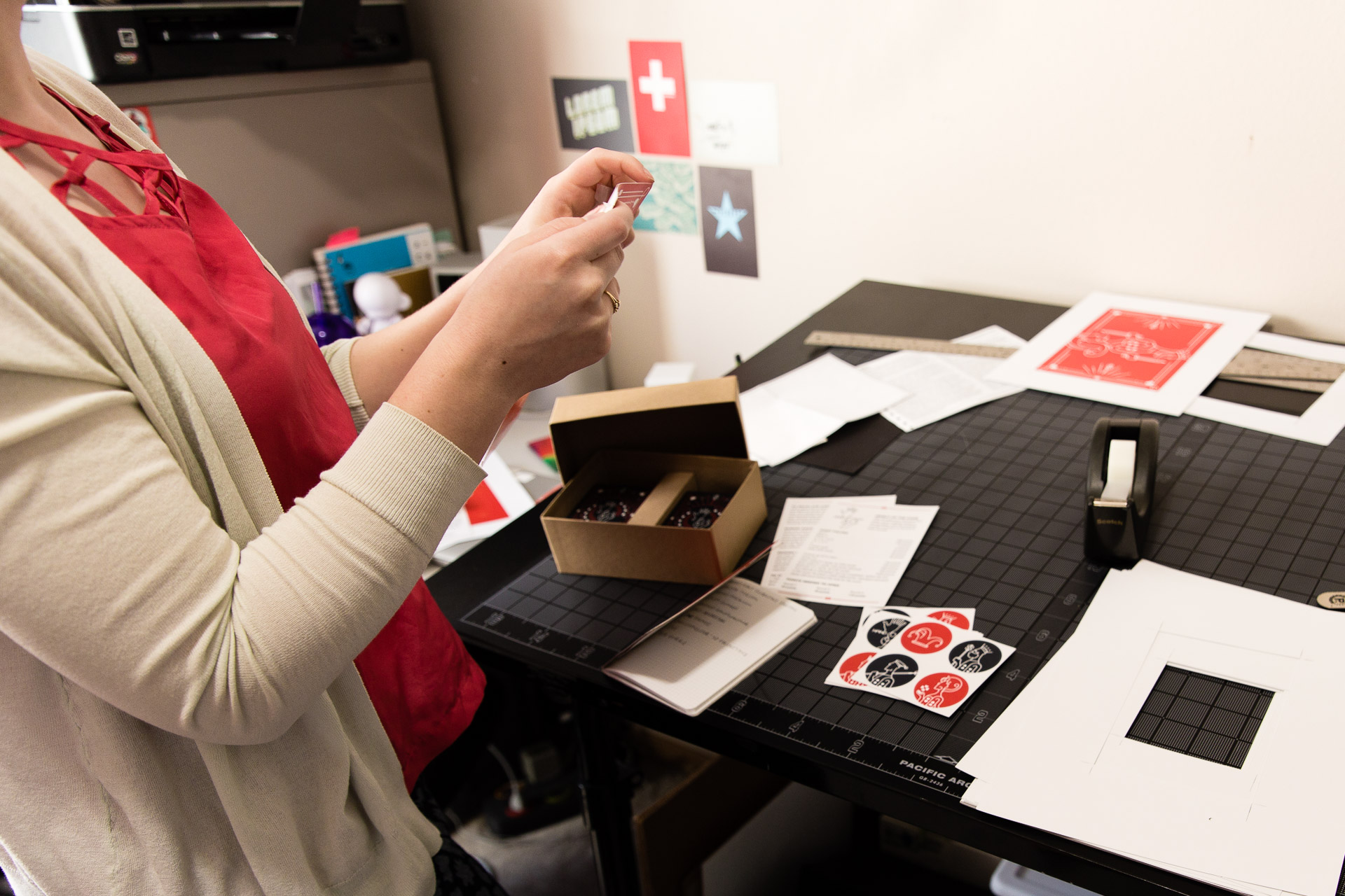 Woman holding cards over black table with a box, stickers, tape dispenser, and paper on it
