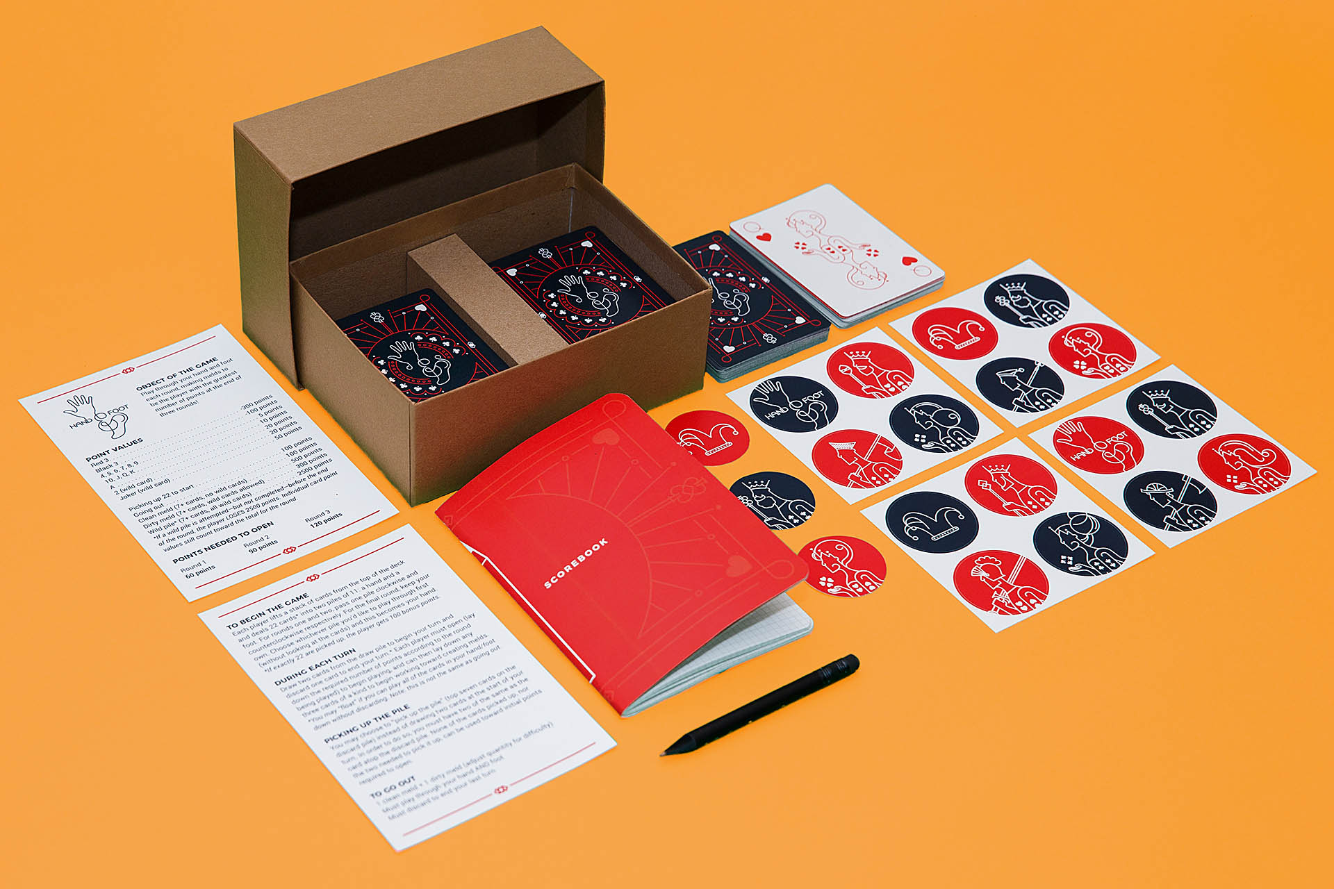 Box of cards, round black and red stickers, red notepad, game rules, and mini black pencil on orange background