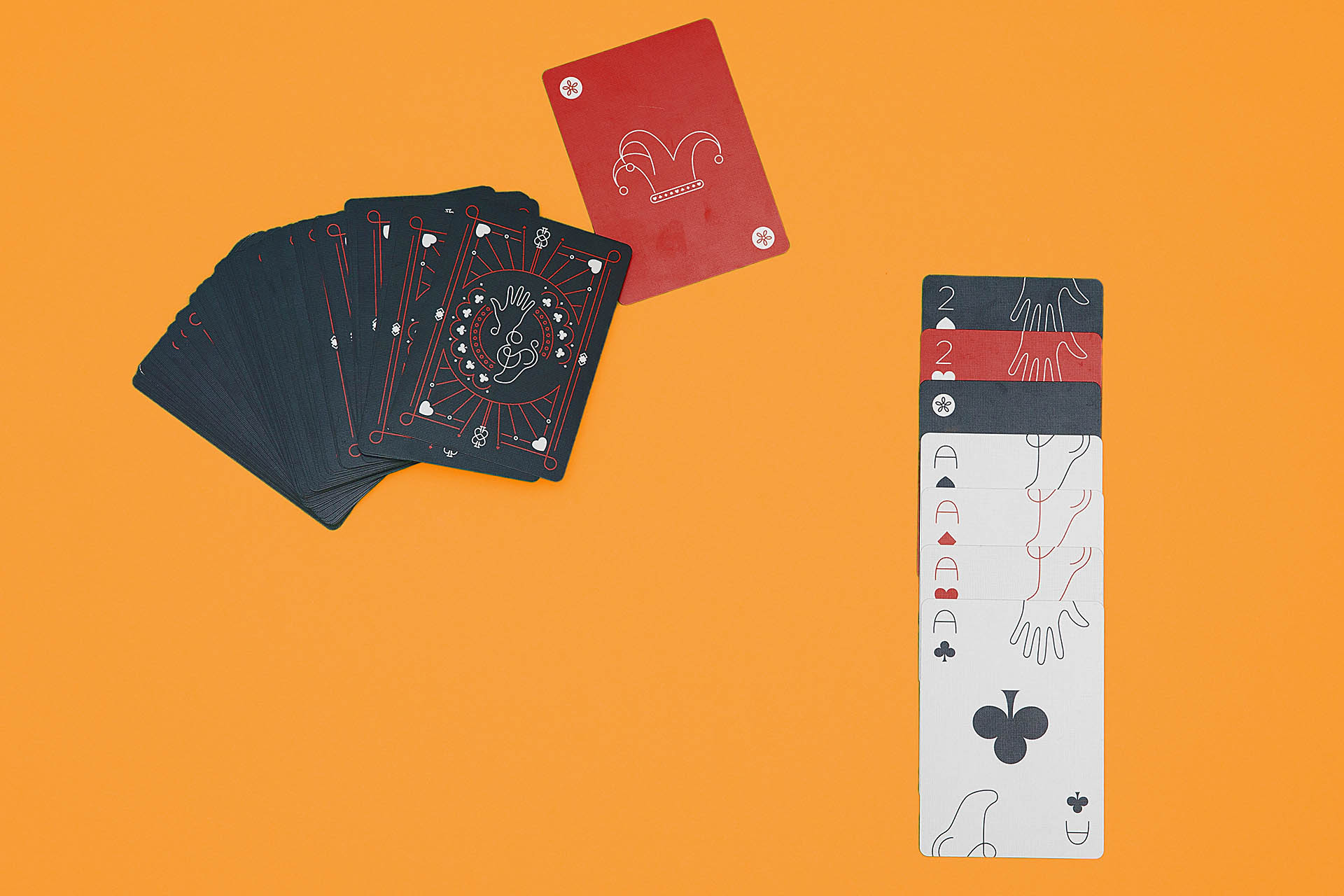 Dark gray backs of cards and a stack of aces face-up on an orange background