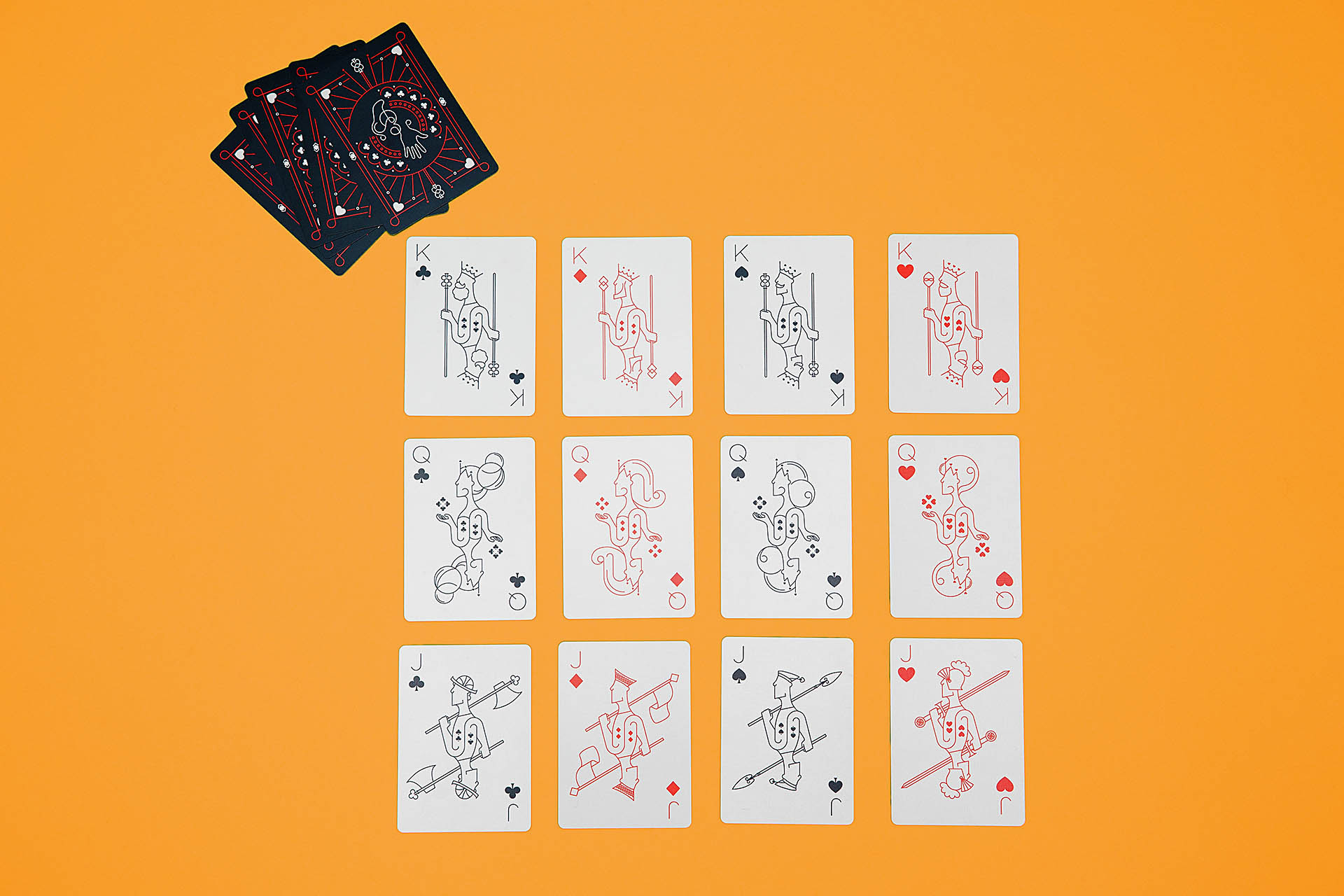 Kings, queens, and jacks laying face-up in a grid on an orange background