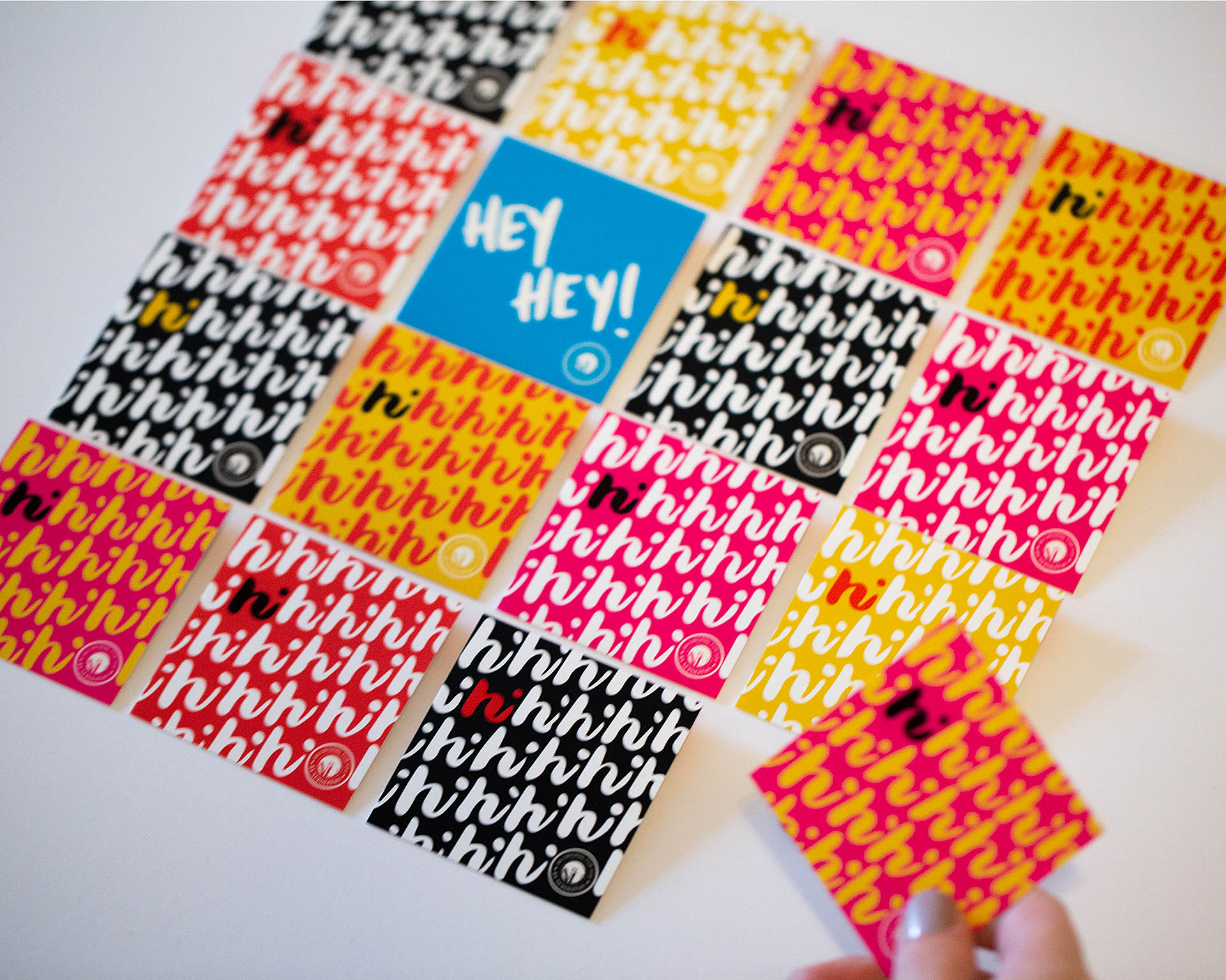 A hand grabbing the corner card out of a grid of colorful square cards