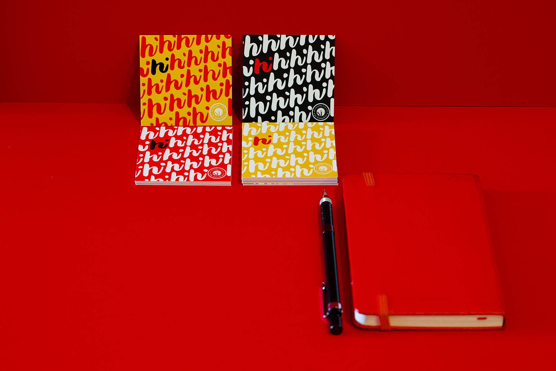 Four colorful cards covered with a repeating hi pattern, a red journal, and black pen on a red background