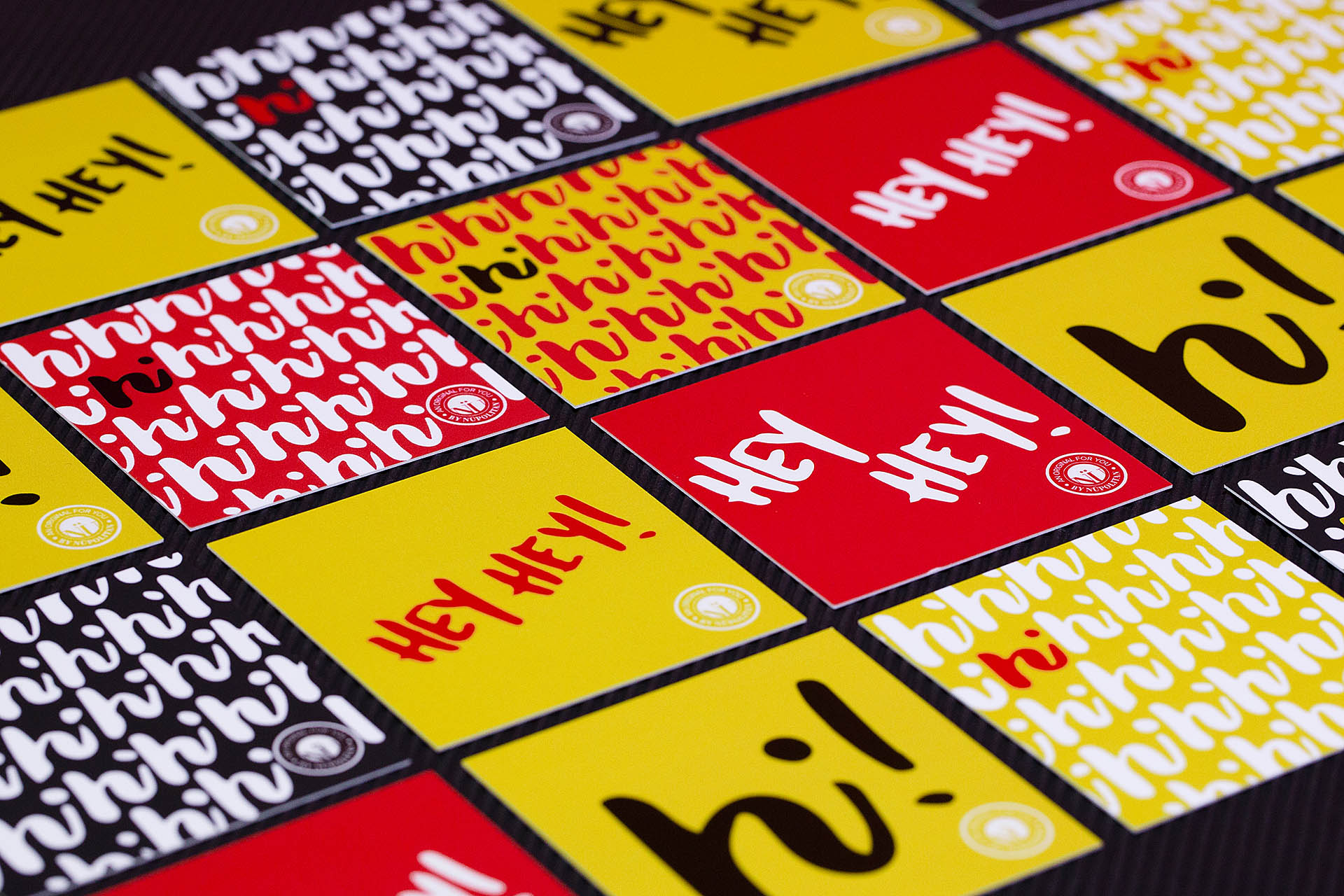 A grid of yellow, red, and black cards with a hi repeating pattern and hey hey printed on them