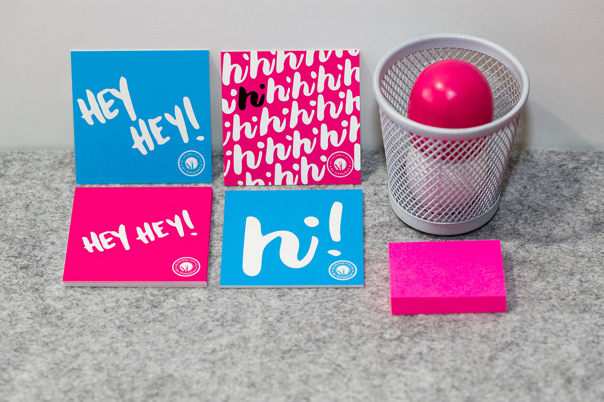 Two blue and two pink cards, a gray pencil cup, and pink post-it notes on gray felt