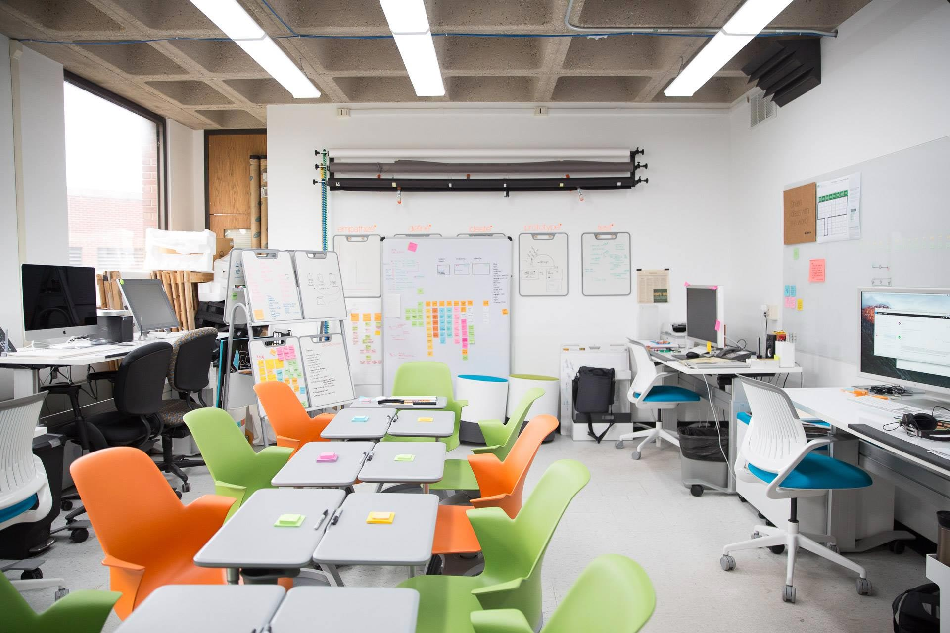 White walled studio with whiteboard, white tables, and gray desks with orange and green chairs