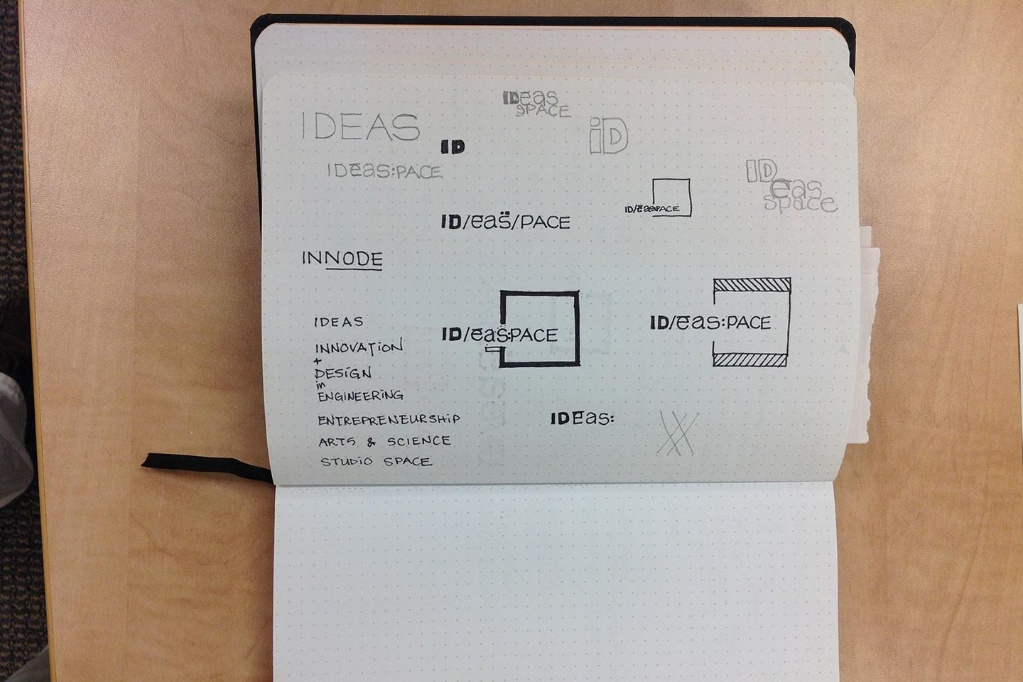 Notebook open to a page displaying logo concepts for ideaspace