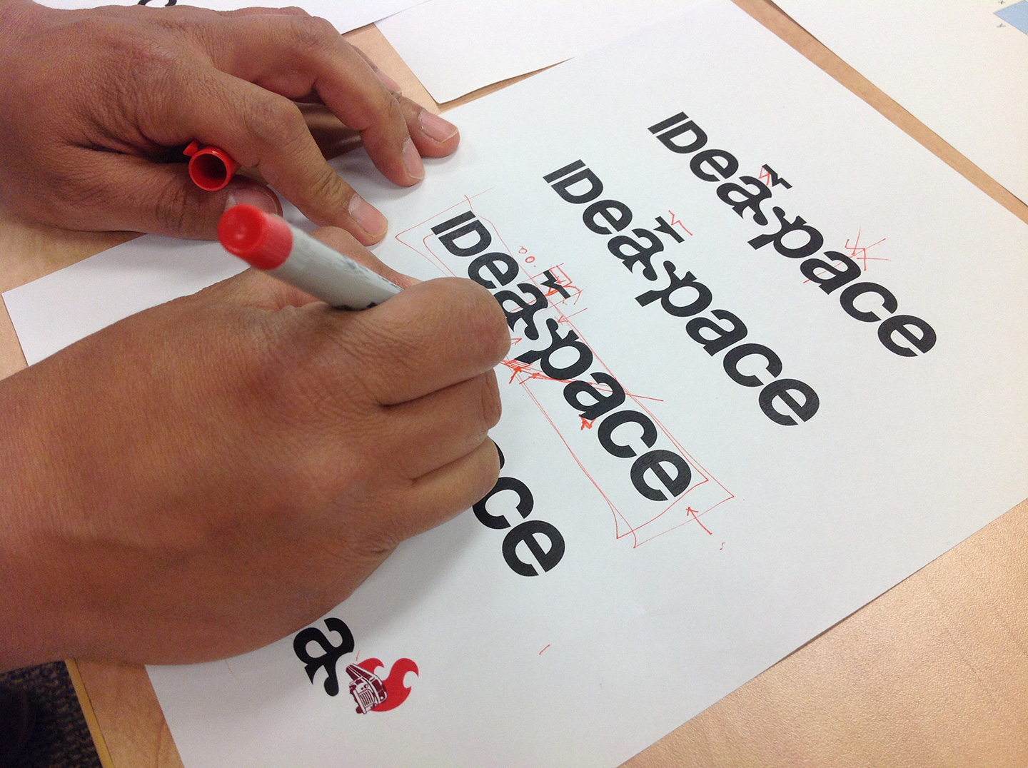 Hands marking up a page featuring IDeaspace logotypes with a red marker