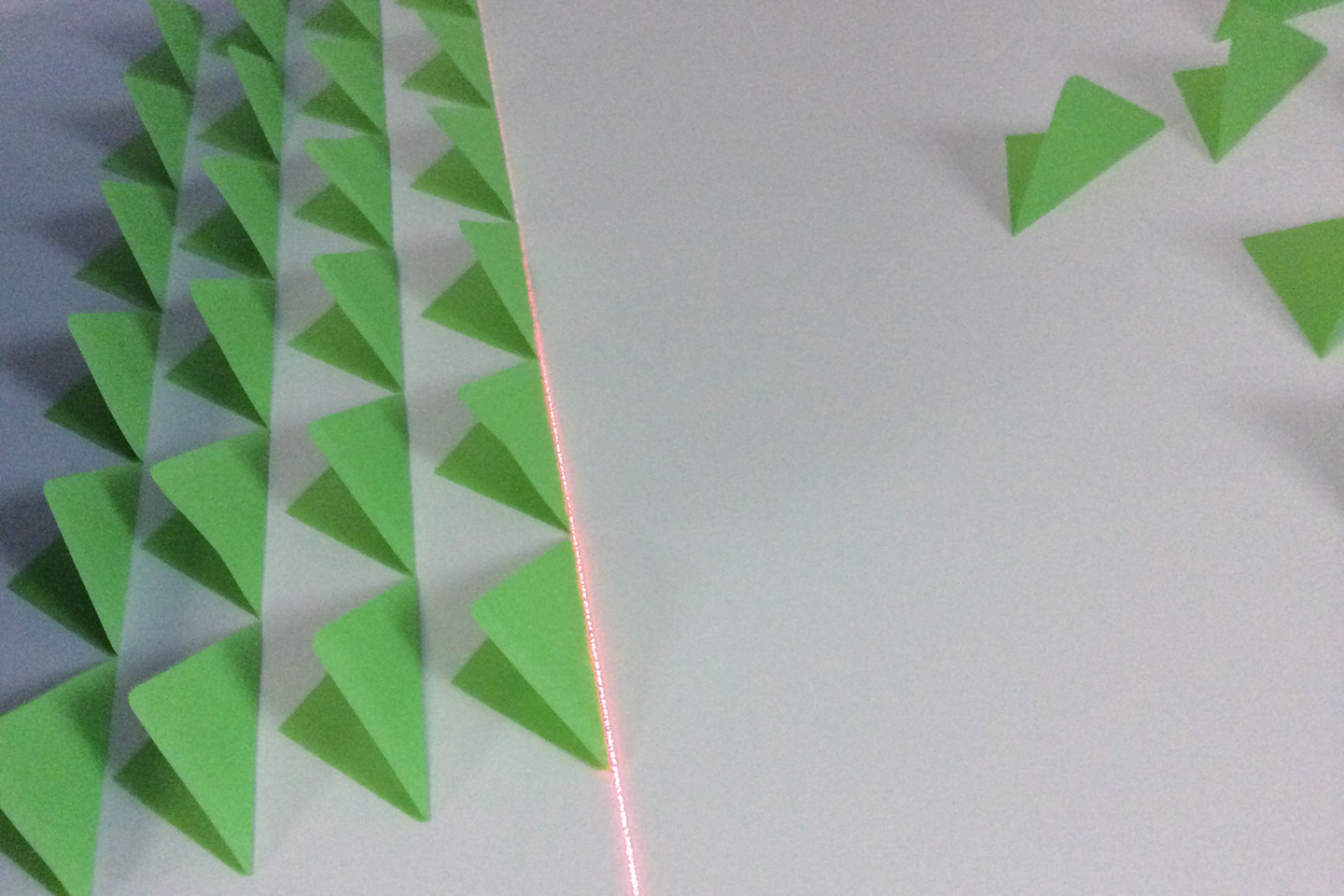 Green post-it notes folded in half on a white wall being aligned by a laser line