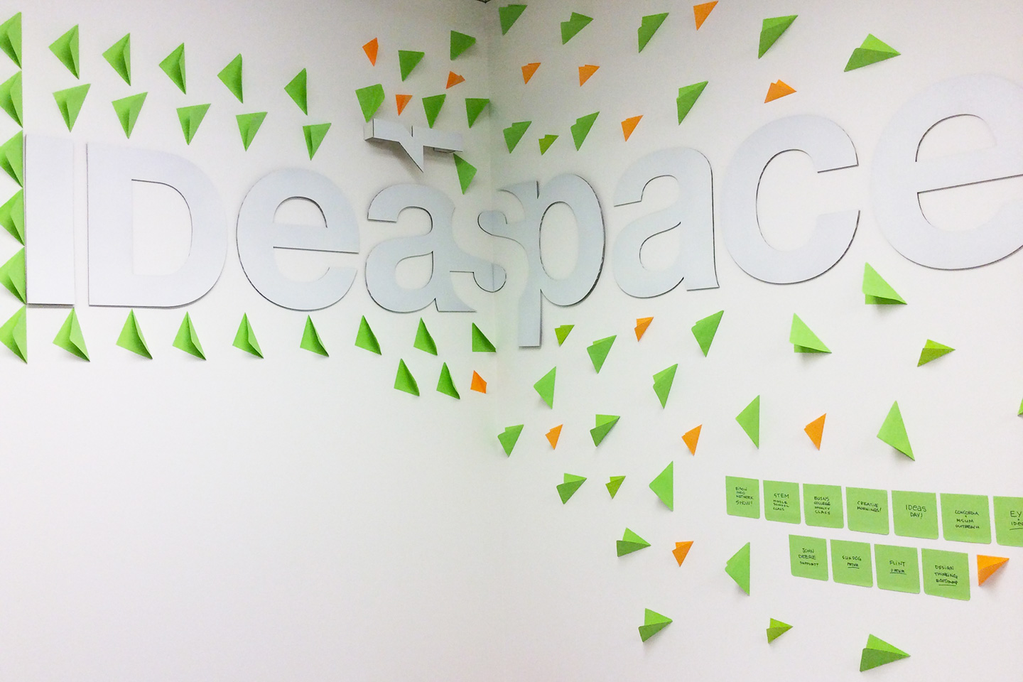 The IDeaspace logotype in white on a white wall surrounded by orange and green post-it notes