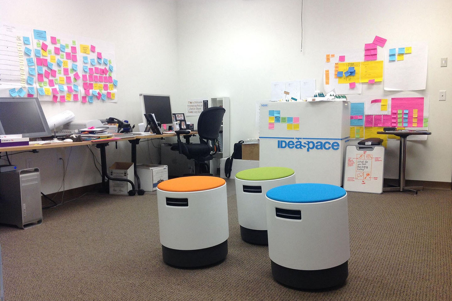 Colorful stools, post-it notes, and two desks in an office with white walls and brown carpet