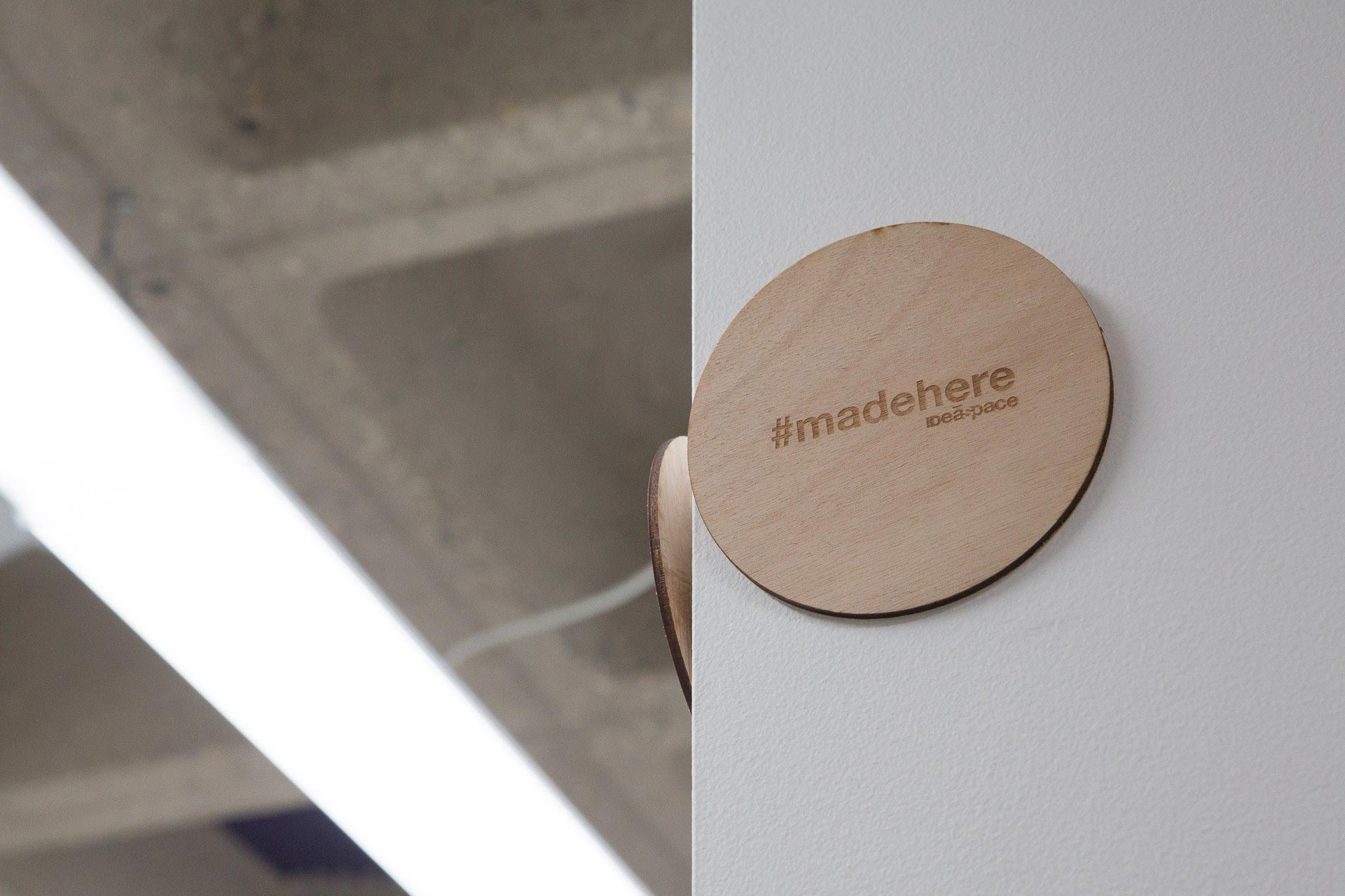 Wooden circle etched with #madehere hanging on the corner of a white wall