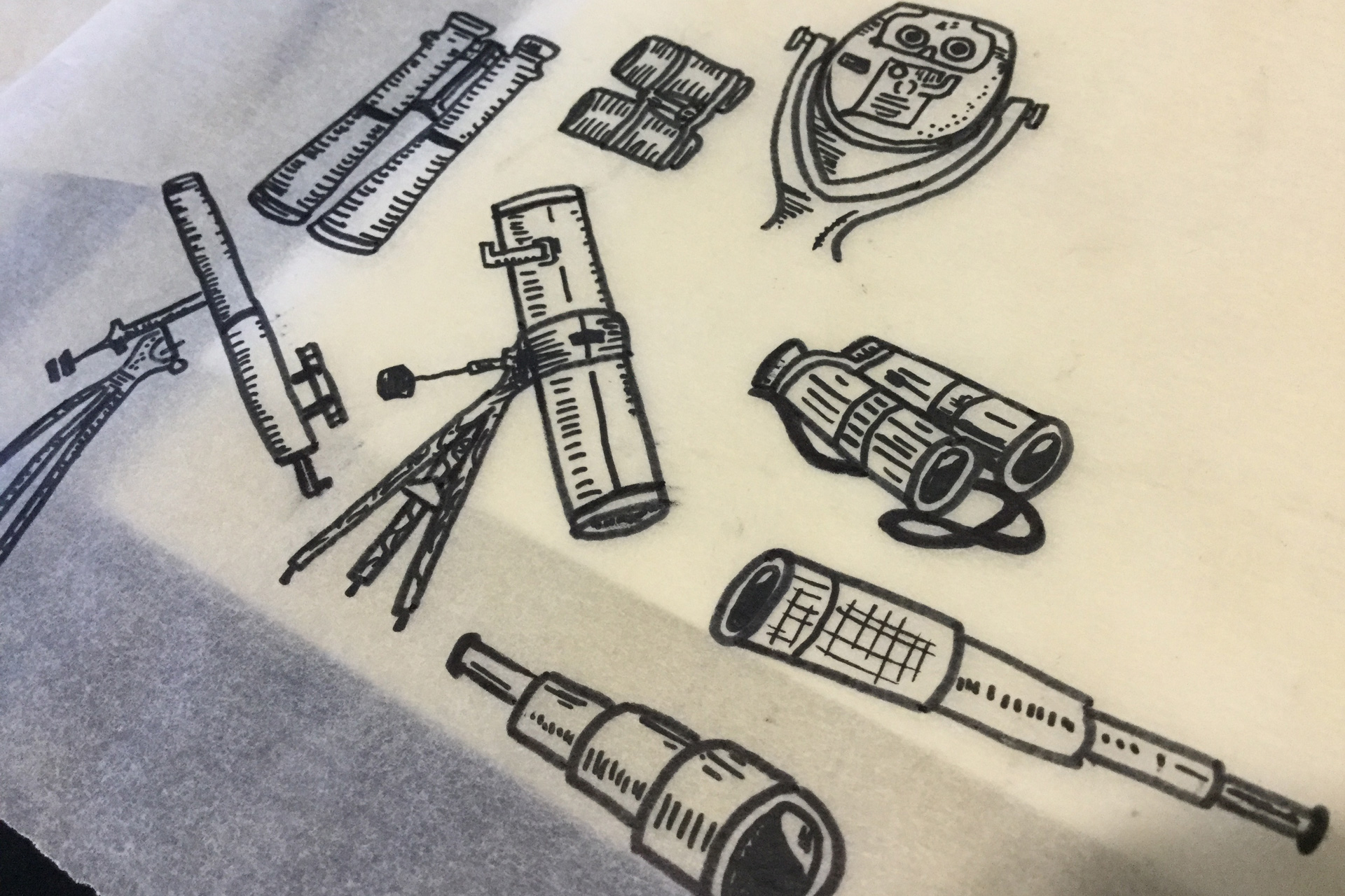 Telescopes and binoculars hand-drawn on a sheet of tracing paper