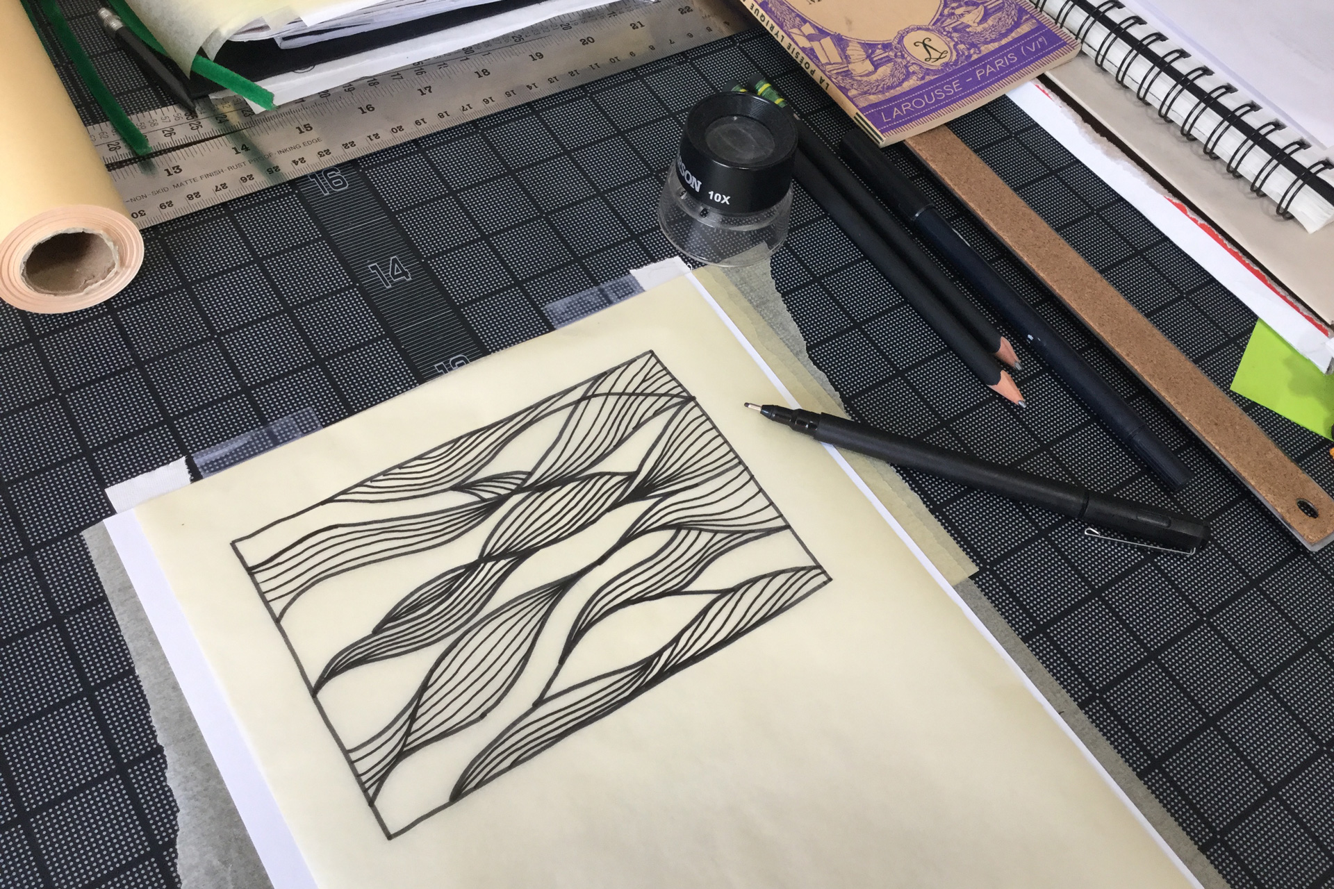 A wavy pattern hand-drawn on a sheet of tracing paper next to pens and notebooks atop a black gridded mat