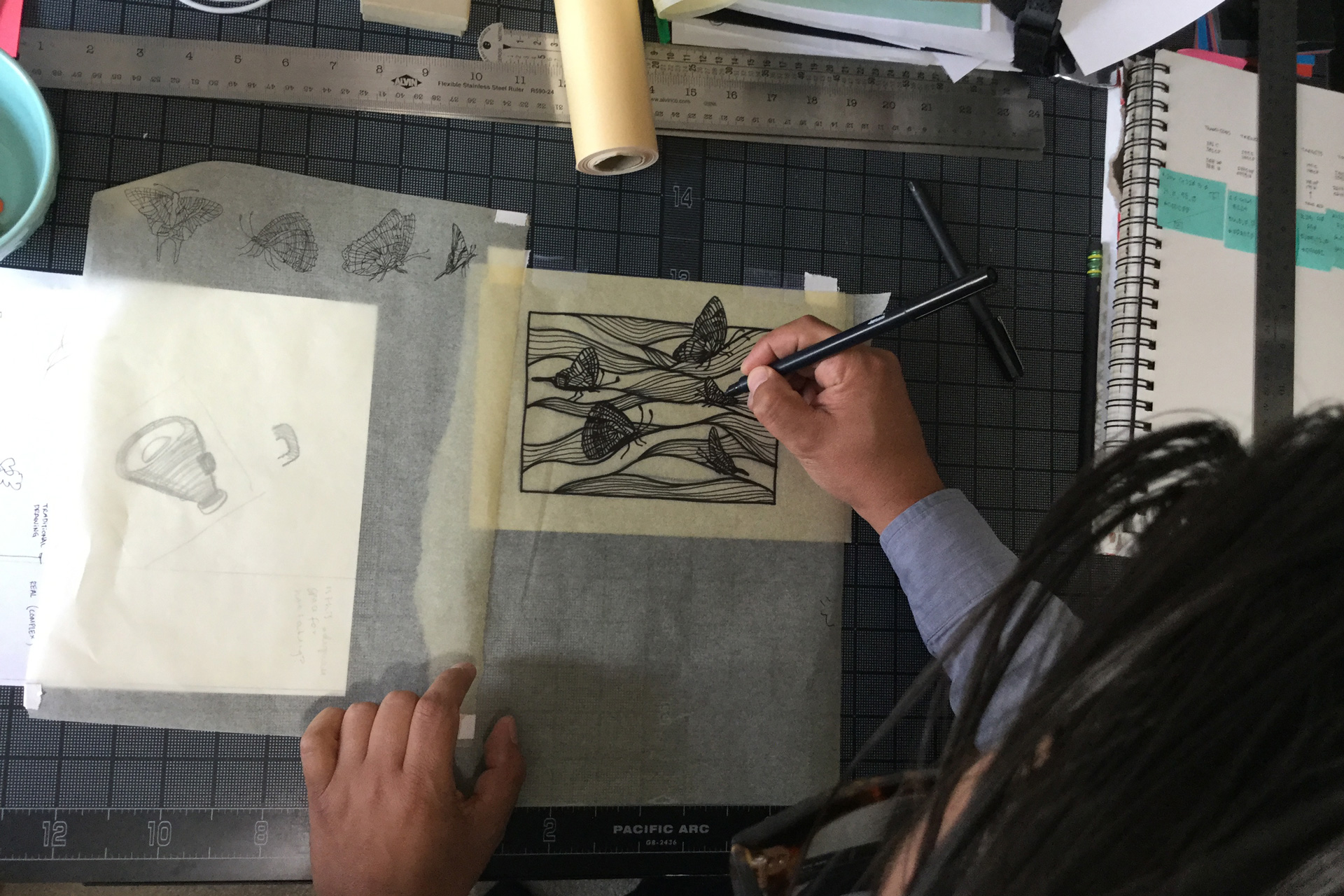 A man drawing waves and butterflies on a piece of tracing paper atop a black gridded mat