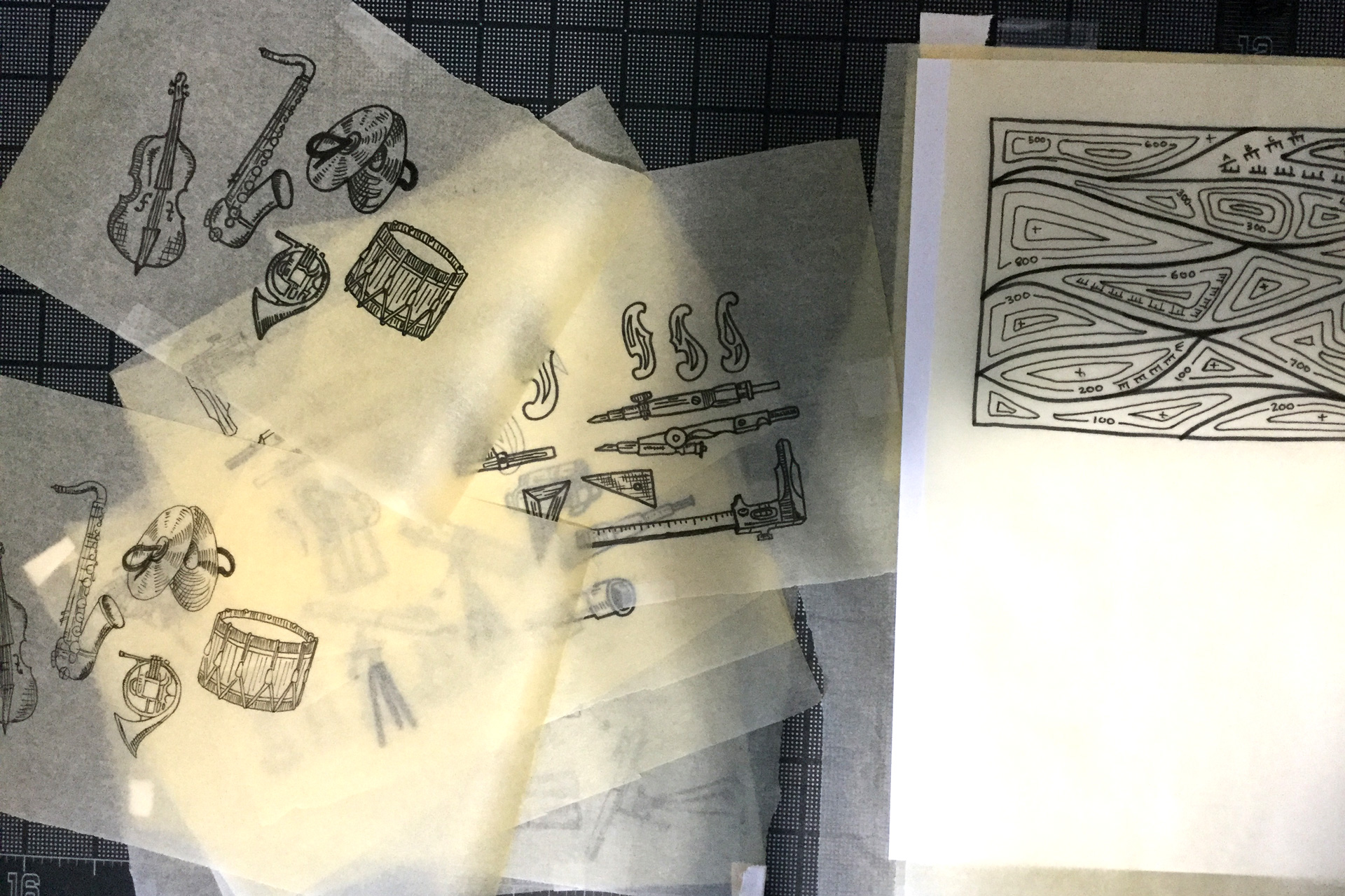 Sheets of tracing paper displaying illustrations of musical instruments