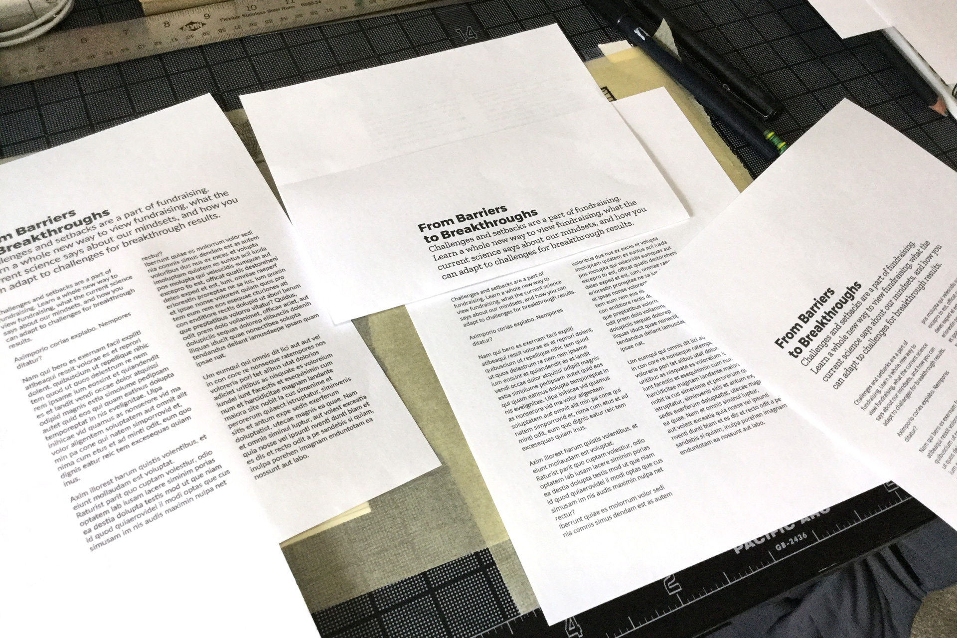 Pieces of white paper with typography samples on a black desk