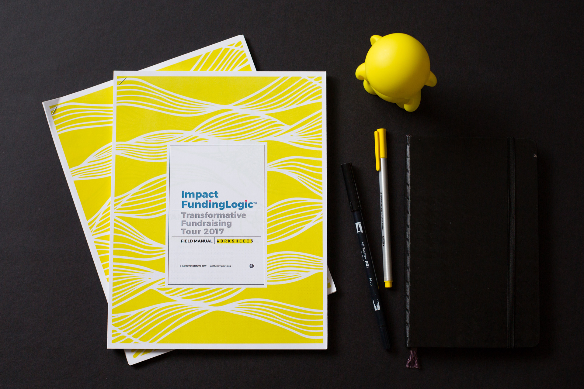Printed Impact FundingLogic packet with yellow cover next to pens and a yellow munny figurine on a black background