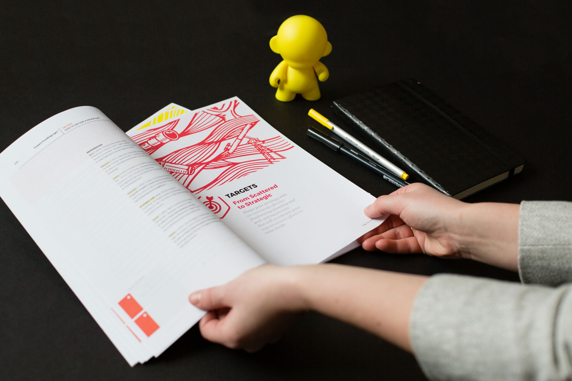 Two hands holding printed materials open next to pens and a yellow munny figurine on a black background