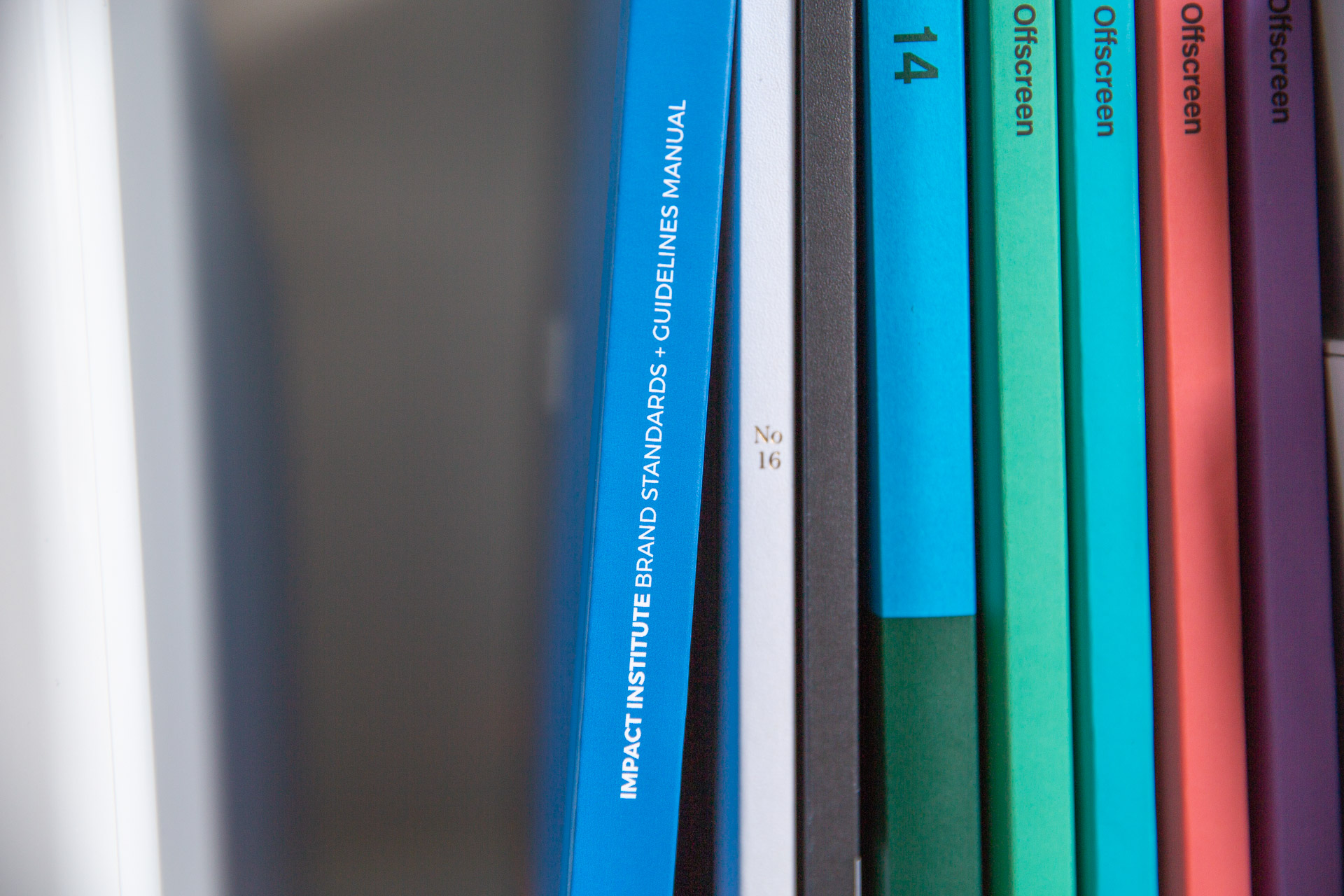 Close-up of Impact Institute brand guideline manual stacked on bookcase next to small, colorful magazines and white bins