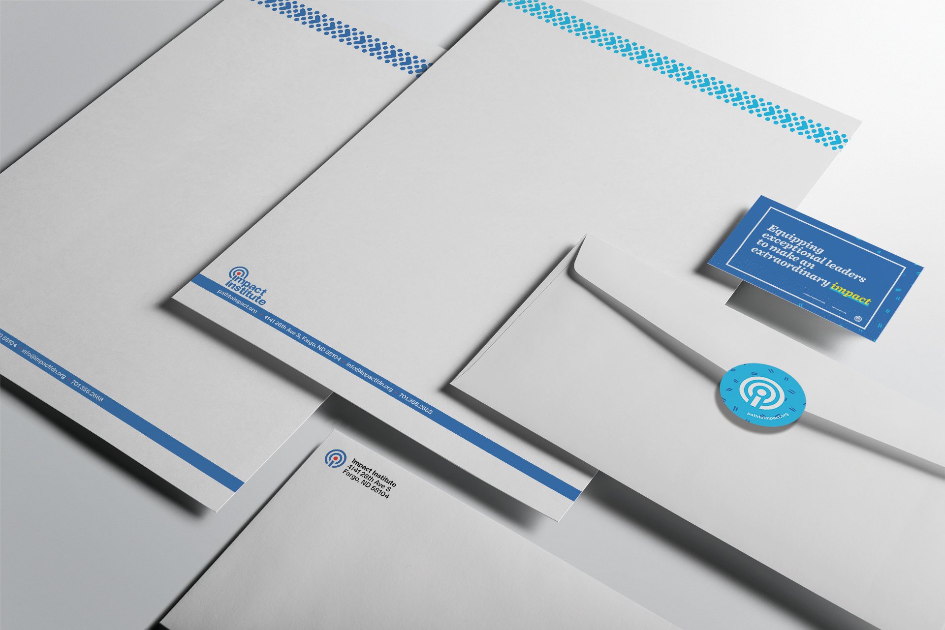 Isometric view of letterhead, envelopes, and business card for Impact Institute